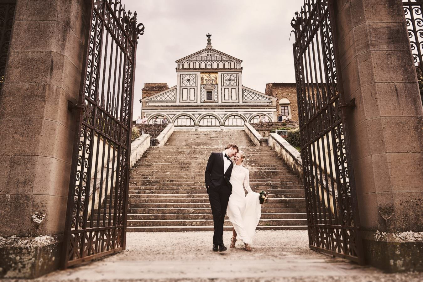 Bride and groom walk through the gate of San Miniato a Monte near Piazzale Michelangelo Florence