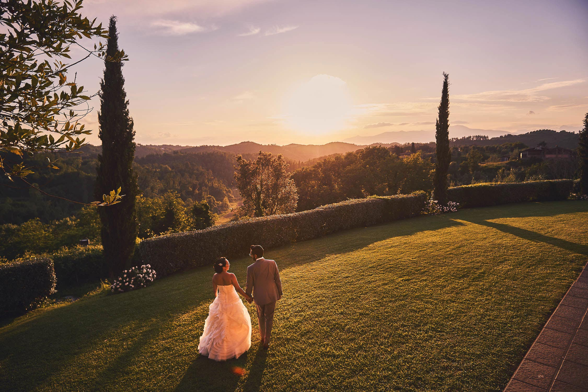 Lovely bride groom portrait walking under Tuscan warm golden sun toward the spectacular countryside
