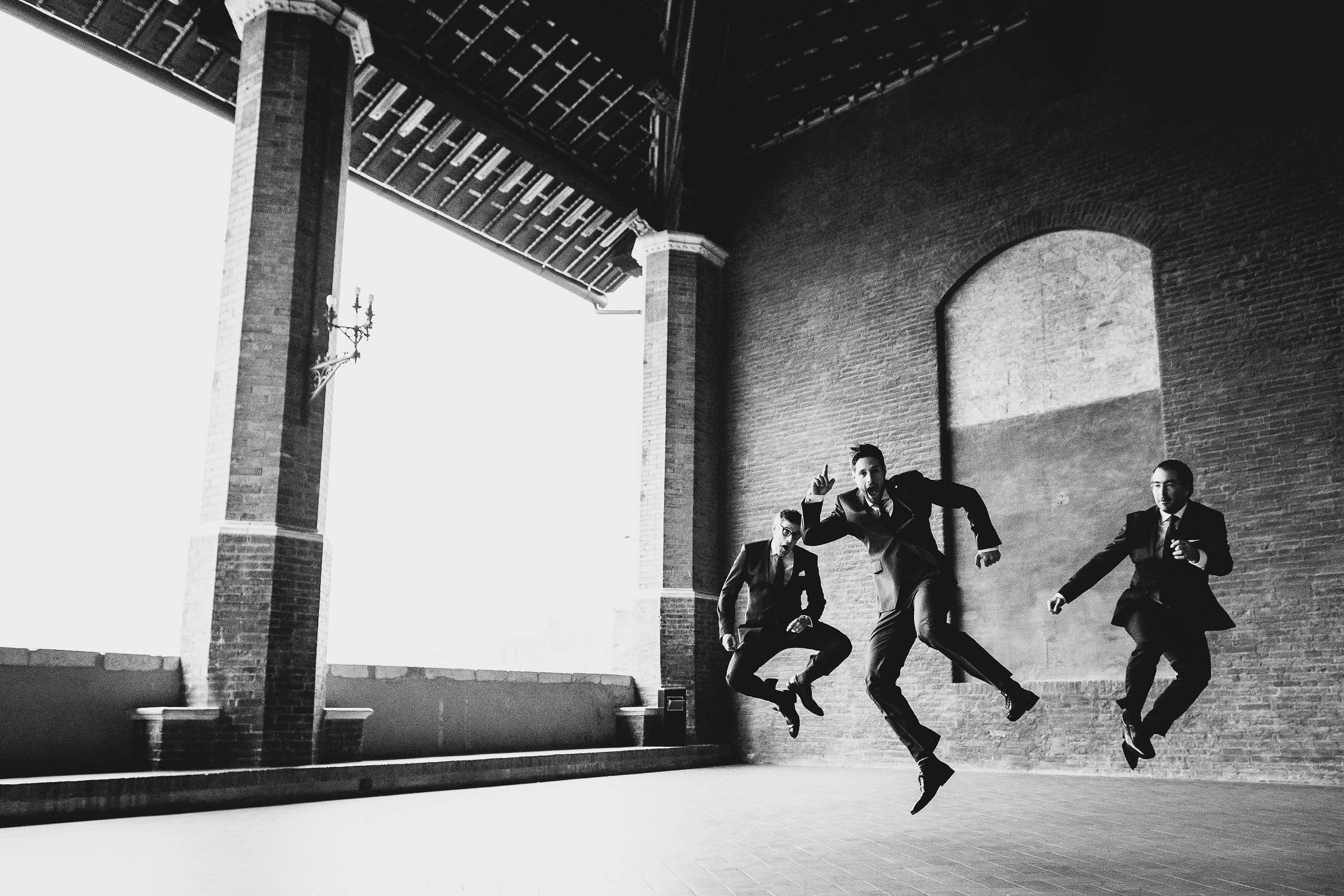 Groom and groomsmen jump just before the civil ceremony into Palazzo Pubblico at Siena