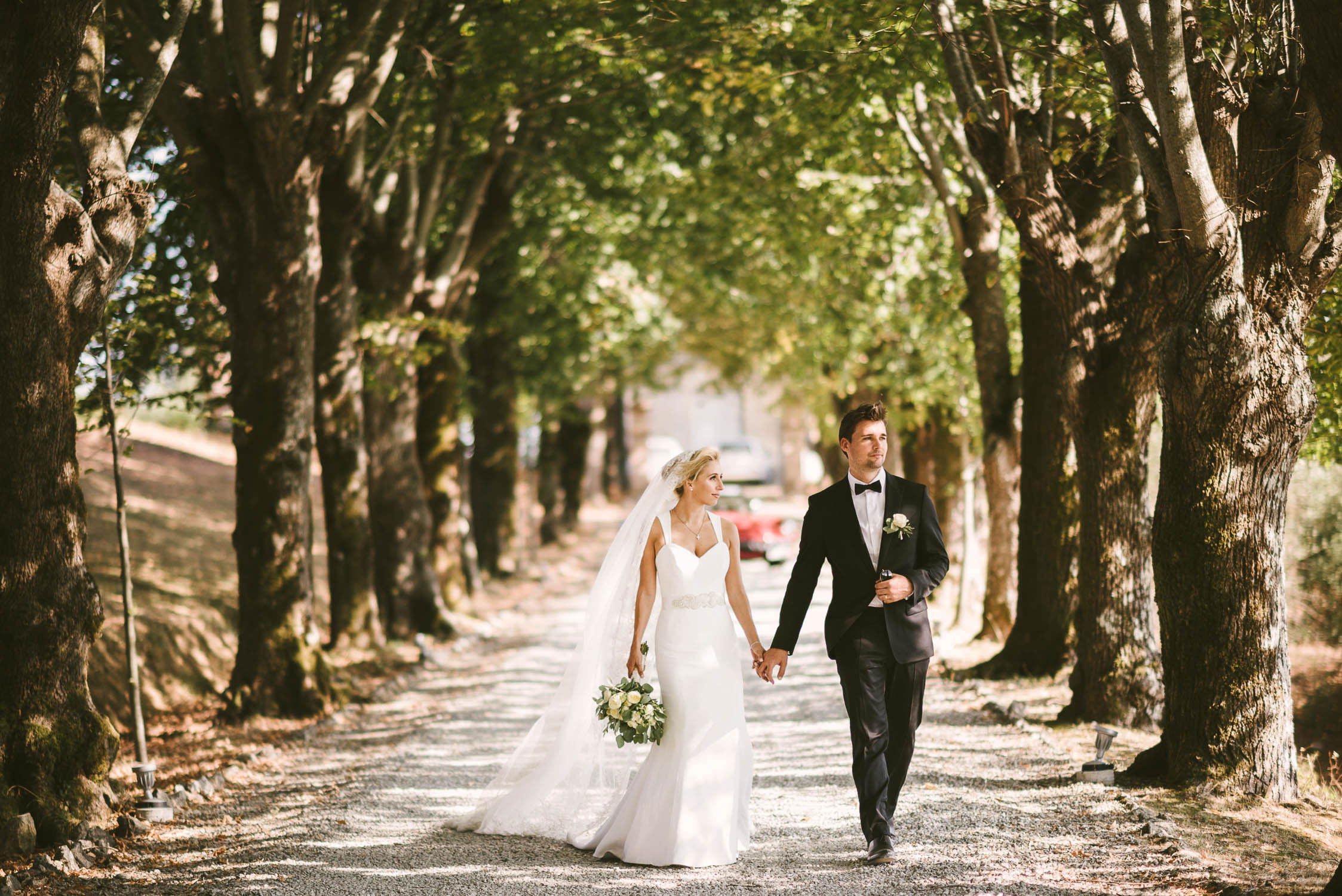 Bride and groom walk into the lovely street of Borgo di Colleoli into the Tuscany countryside