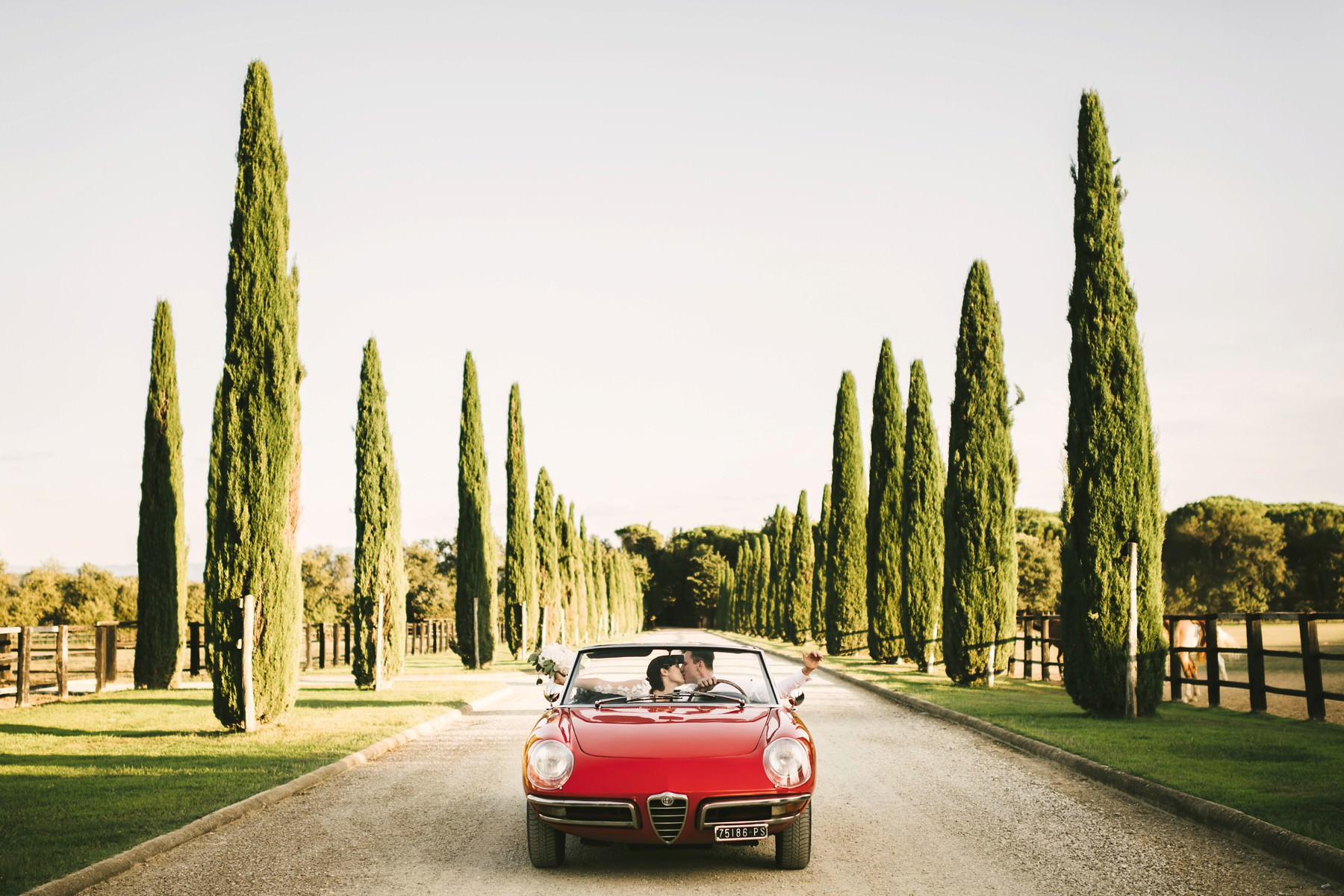Bride and groom special kiss on Alfa Romeo vintage car in cypress road near Montelucci Country Resort