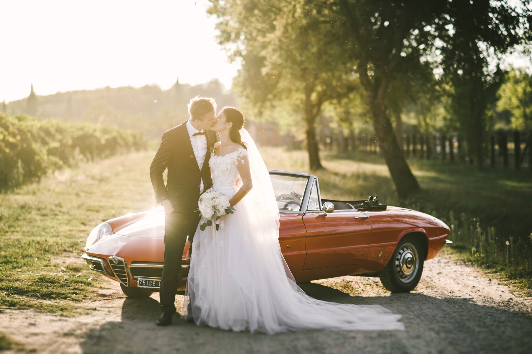 Bride and groom wedding portrait with old vintage car Alfa Romeo spider