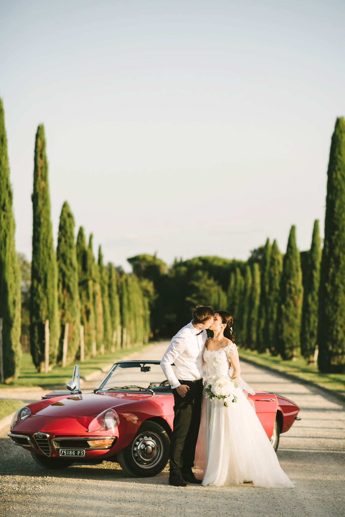 Bride and groom special kiss on Alfa Romeo spider vintage car in cypress road near Montelucci Country Resort