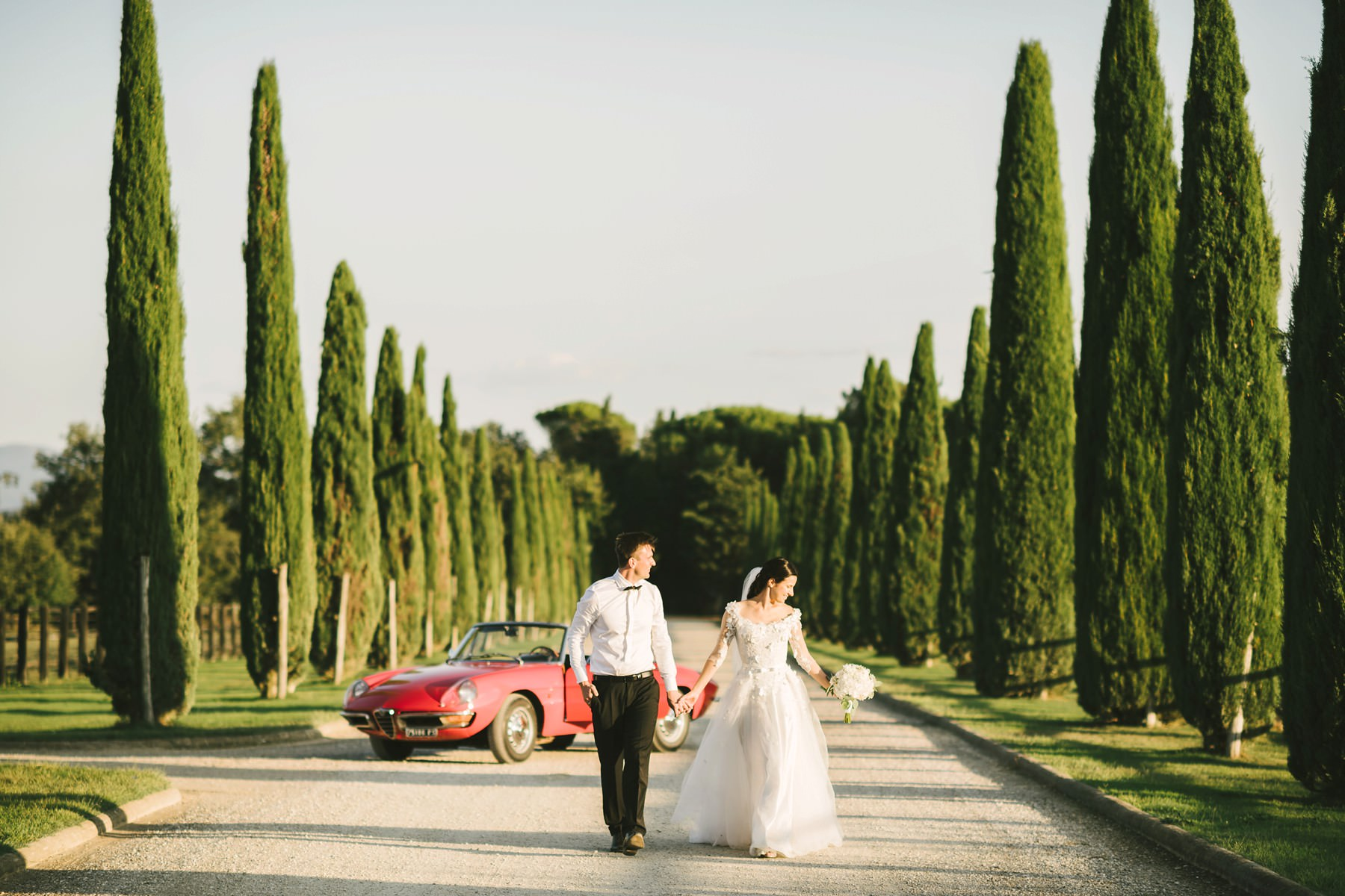 Bride and groom walks in a lovely Tuscan cypress road near Montelucci Country Resort