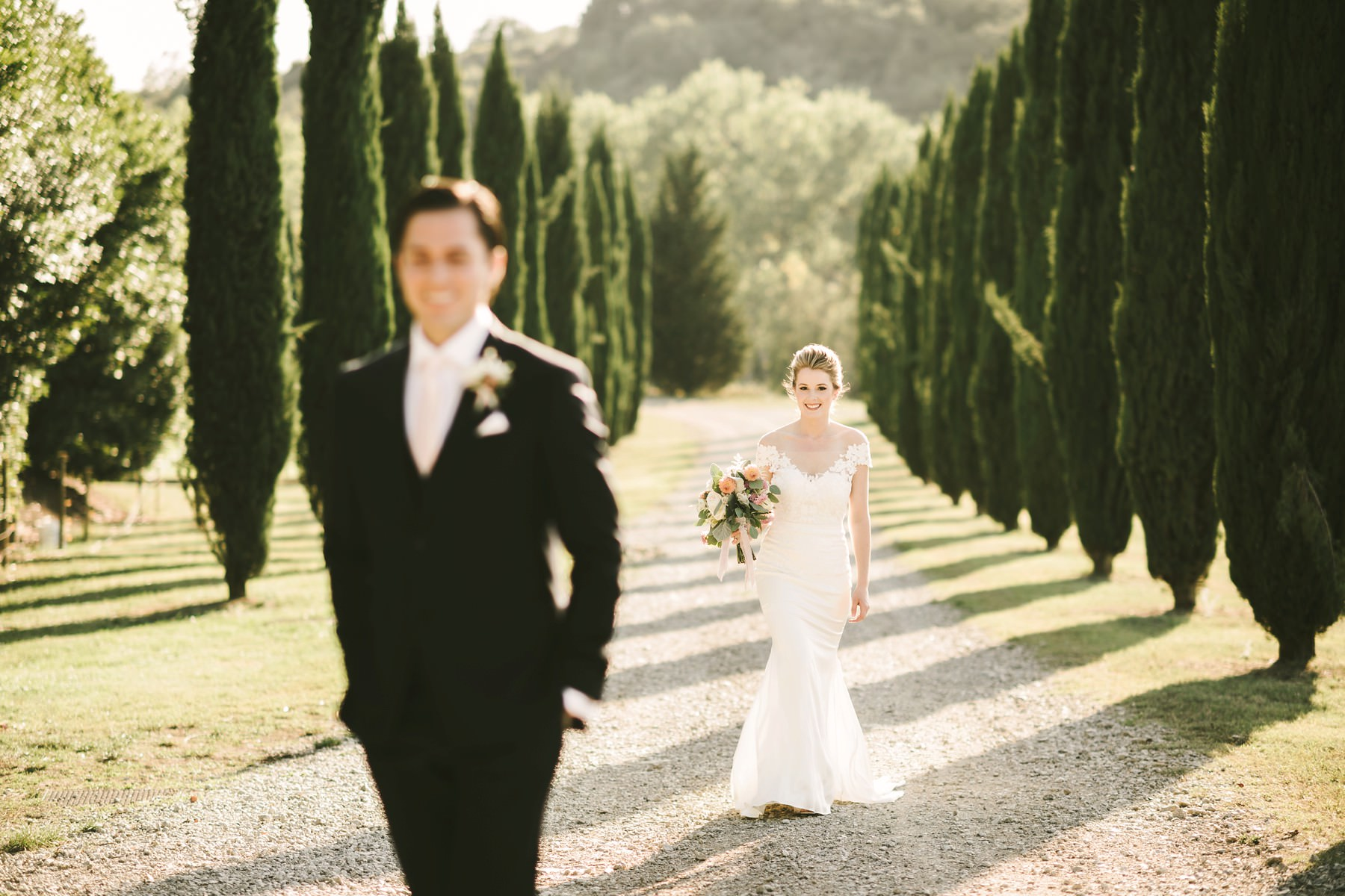 Bride and groom first look in evocative Tuscan cypress road at Villa La Selva Wine Resort