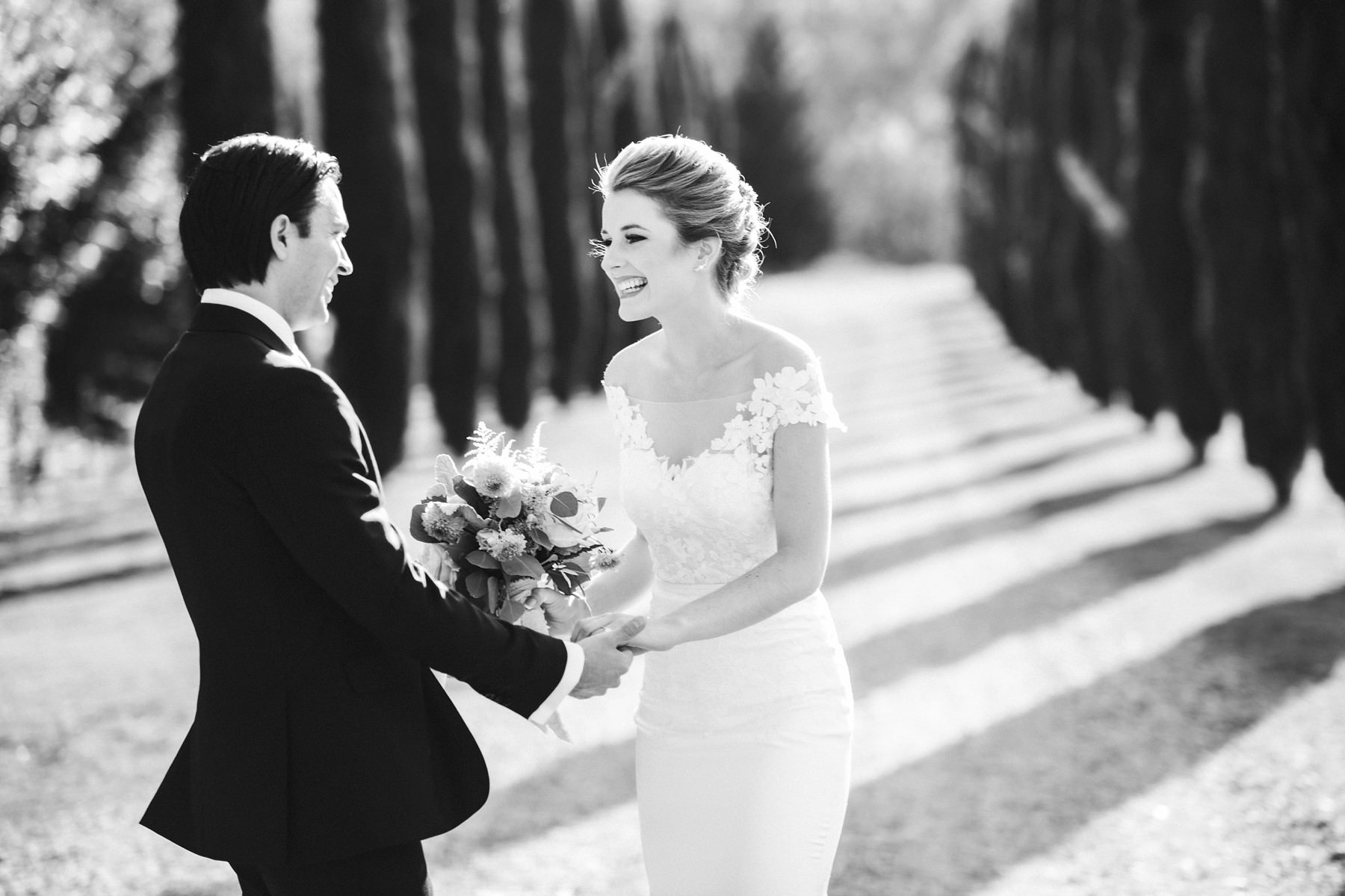 Lovely moment by bride and groom during their first look in Tuscan cypress road at Villa La Selva resort, Tuscany