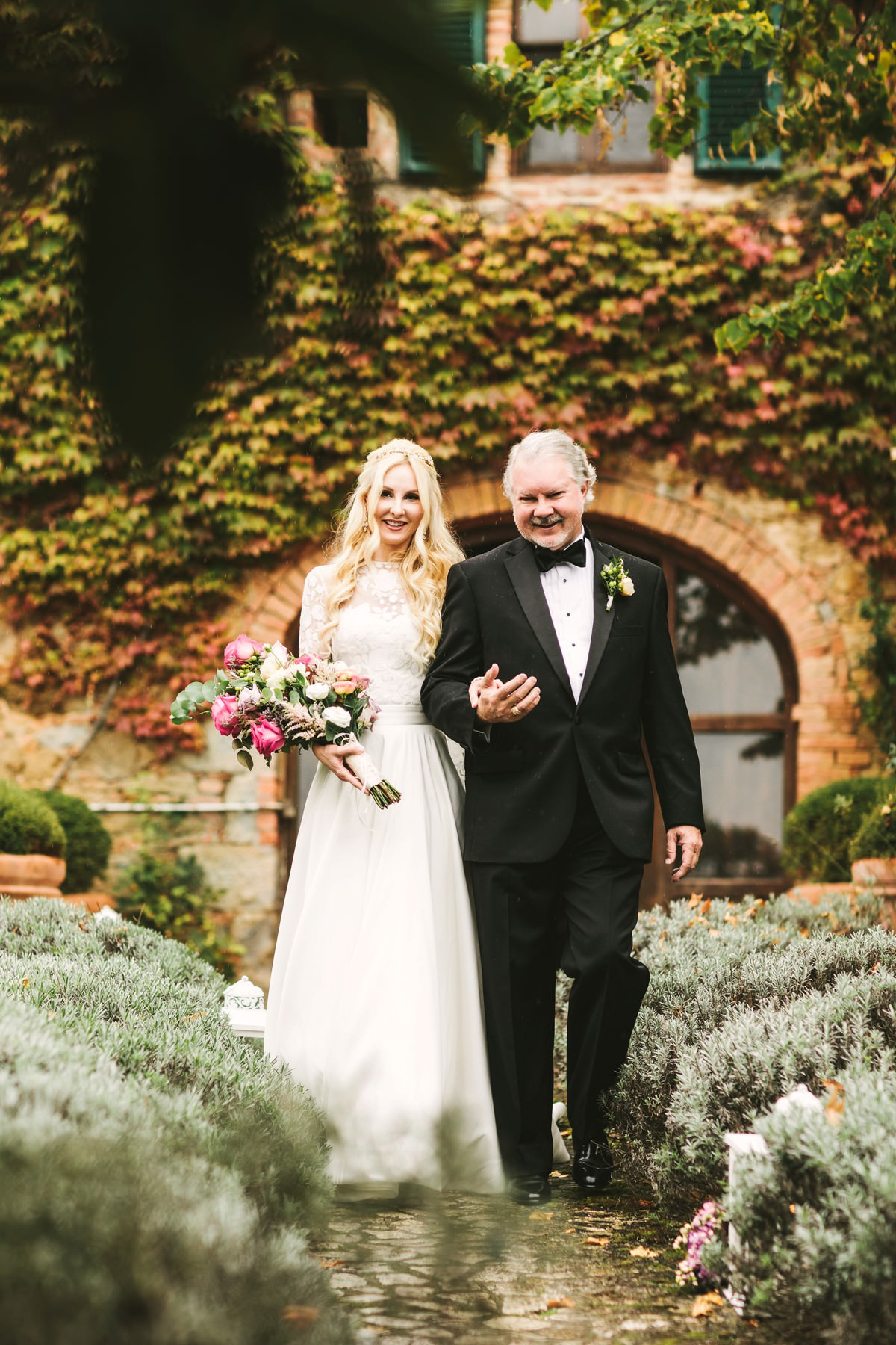 Bride and father wlak to the groom. Outdoor ceremony in Tuscany Val D'Orcia wedding