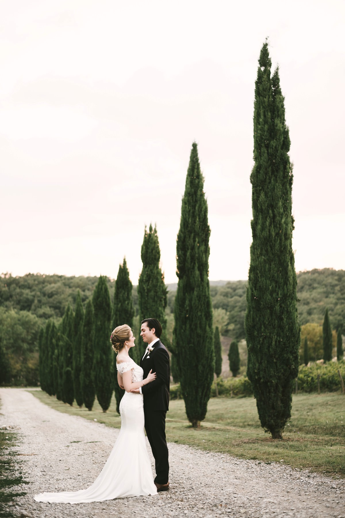 Lovely couple portrait in the evocative cypress road of Villa La Selva Resort in the countryside of Tuscany