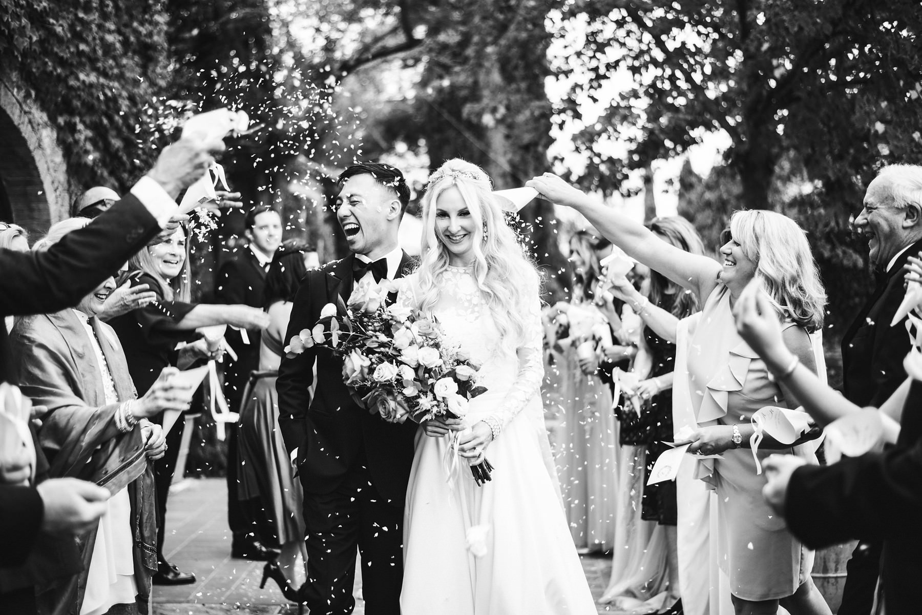 Beautiful and exciting wedding shoot with petal throwing after intimate wedding ceremony celebrated in the farmhouse Podere Fornace in Val D'Orcia area of Tuscany