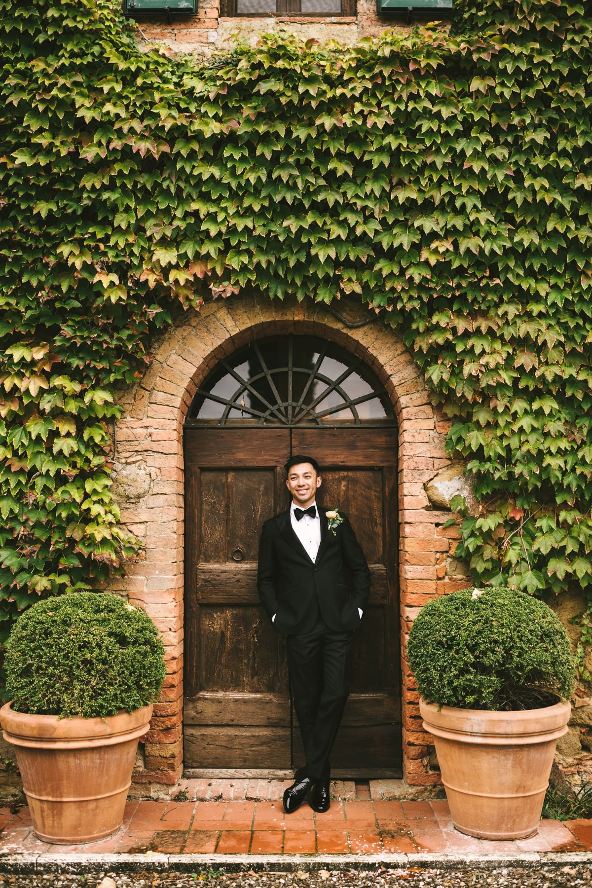 Groom portrait in front of an ancient door in the lovely and beautiful wedding venue of La Fornace in countryside of Tuscany