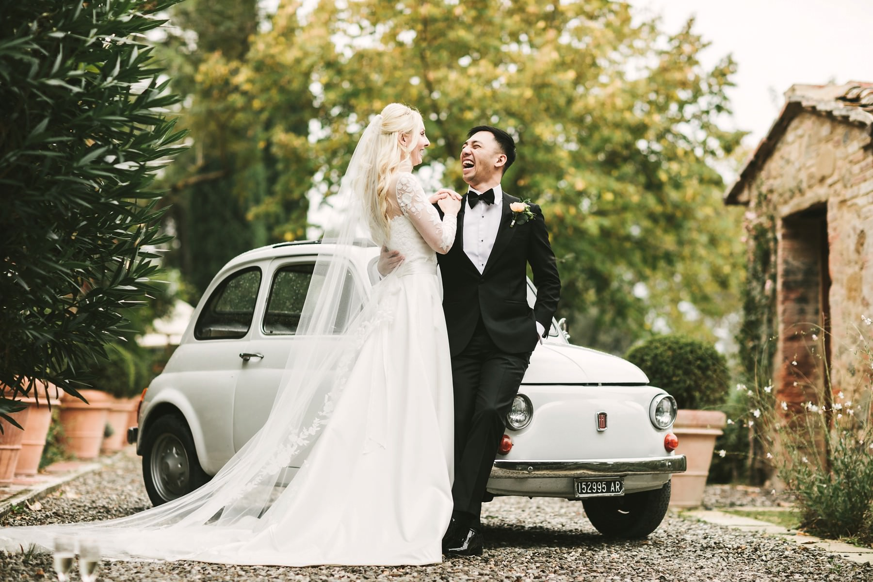 Exciting bride and groom wedding portrait with Fiat 500
