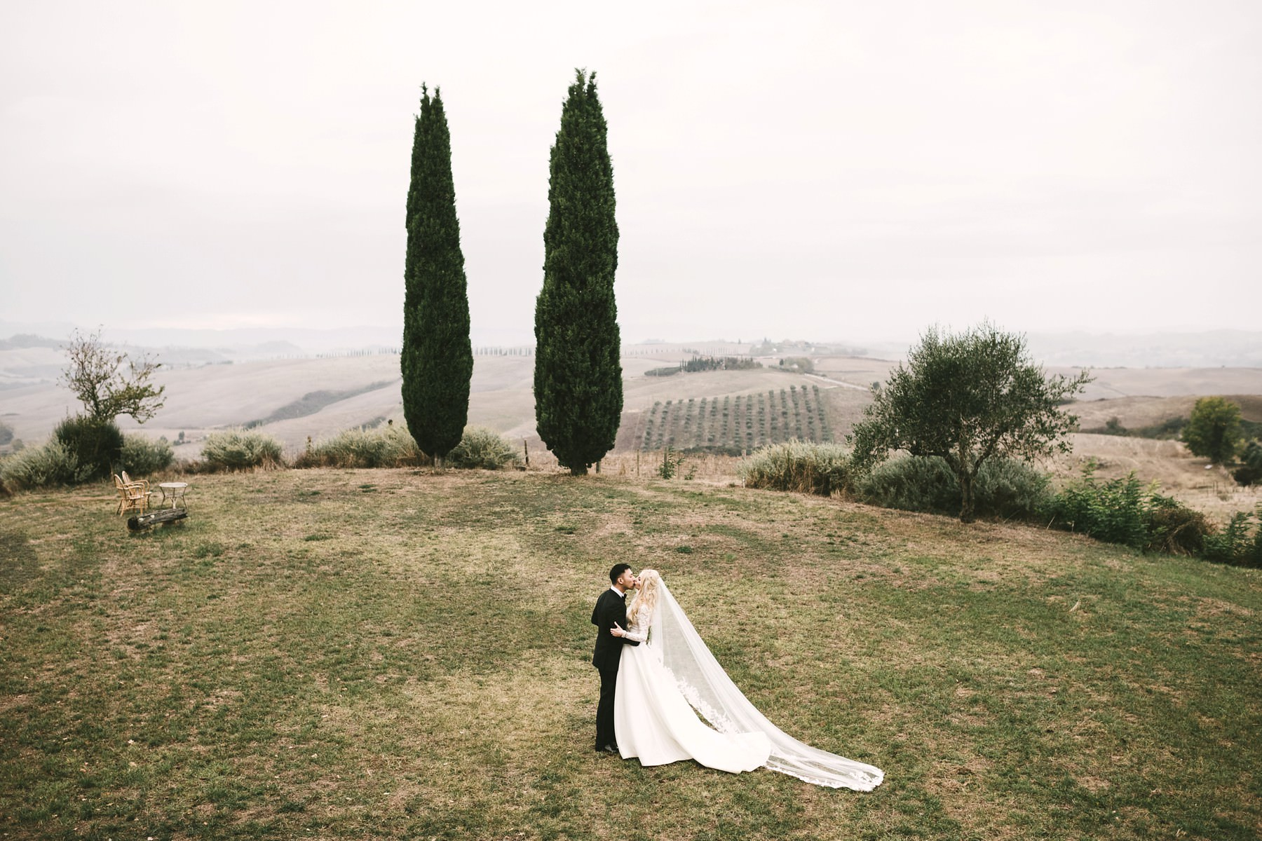 Bride groom wedding photo into the Tuscany Val D'Orcia countryside with evocative cypress trees