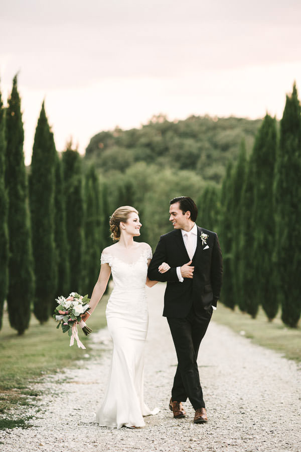 Bride and groom candid portrait in the evocative cypress road of Villa La Selva Resort in the countryside of Tuscany