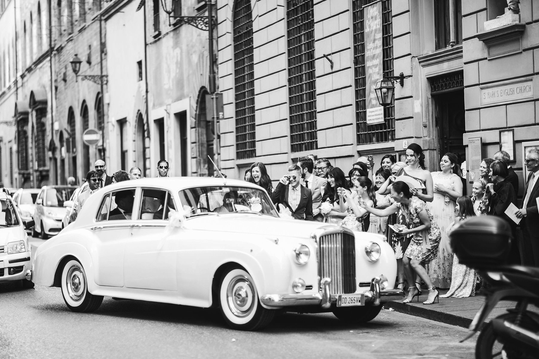 Exciting moment while bride and groom leave the St. Mark Church in Florence for the portrait session. Intimate destination wedding in Florence