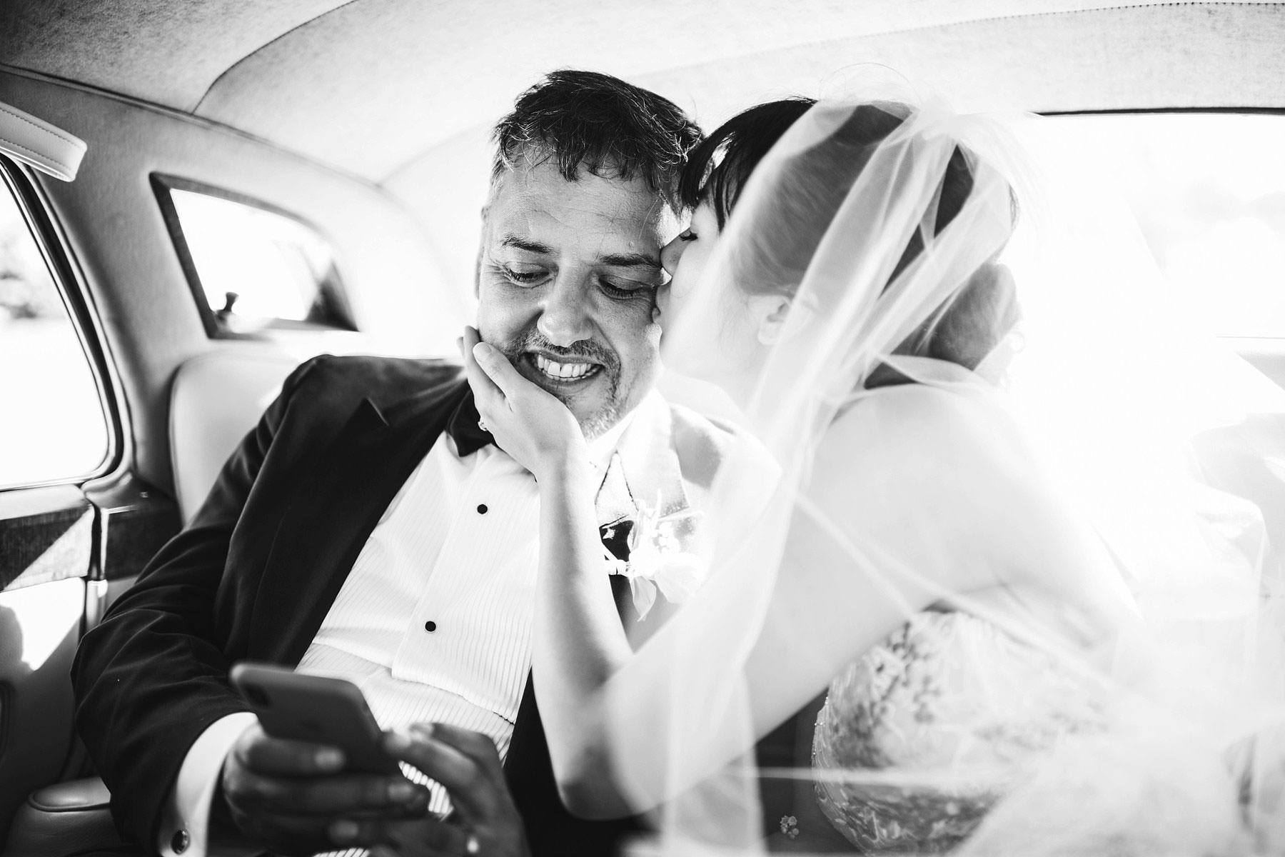 Lovely candid and delicate moment by bride and groom while seated in vintage luxury car. Intimate destination wedding in Florence