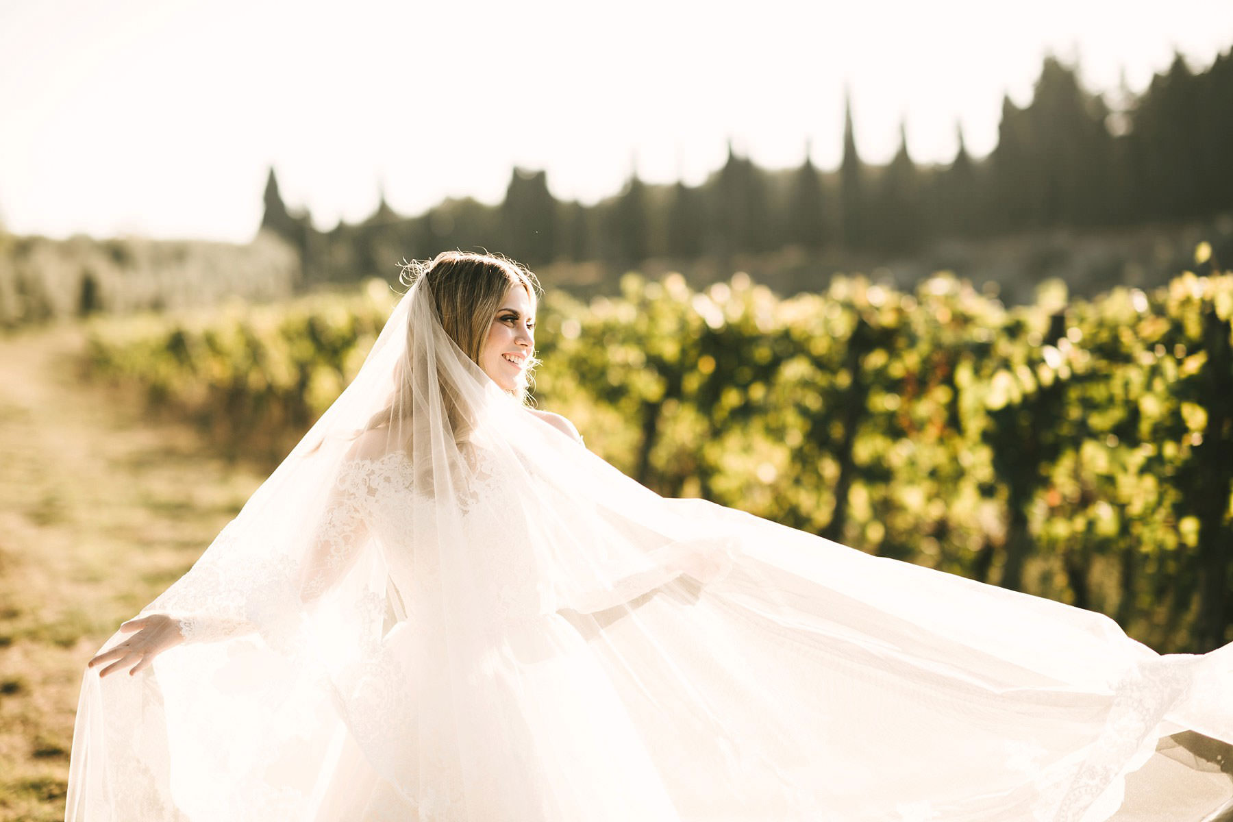 Elegant and beautiful bride Cecily in gorgeous Justin Alexander wedding gown under the Tuscan sun. Bridal wedding portrait in Chianti vineyard near Villa Mangiacane