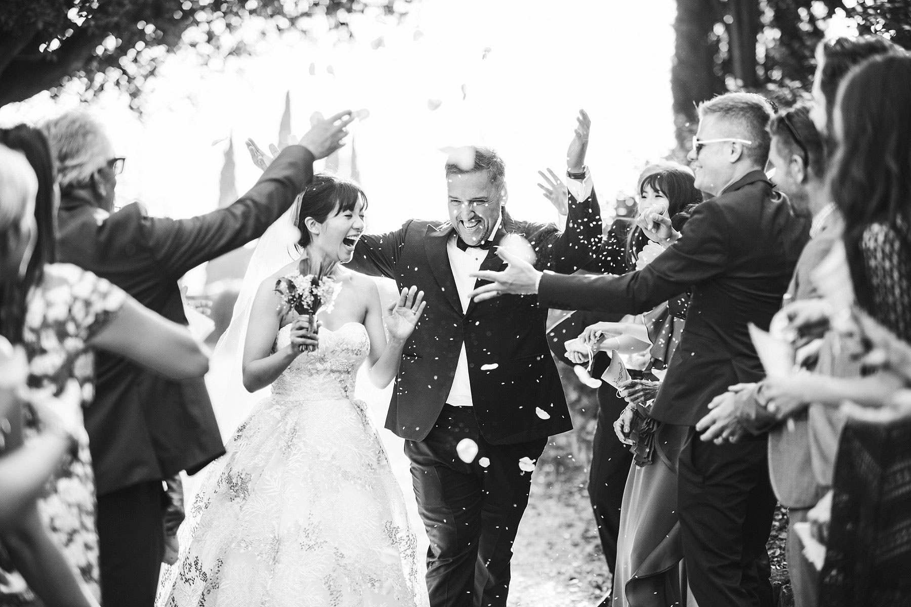 Gorgeous and exciting wedding photo during petal throwing at Villa Le Fontanelle for this elegant and intimate destination marriage in Florence