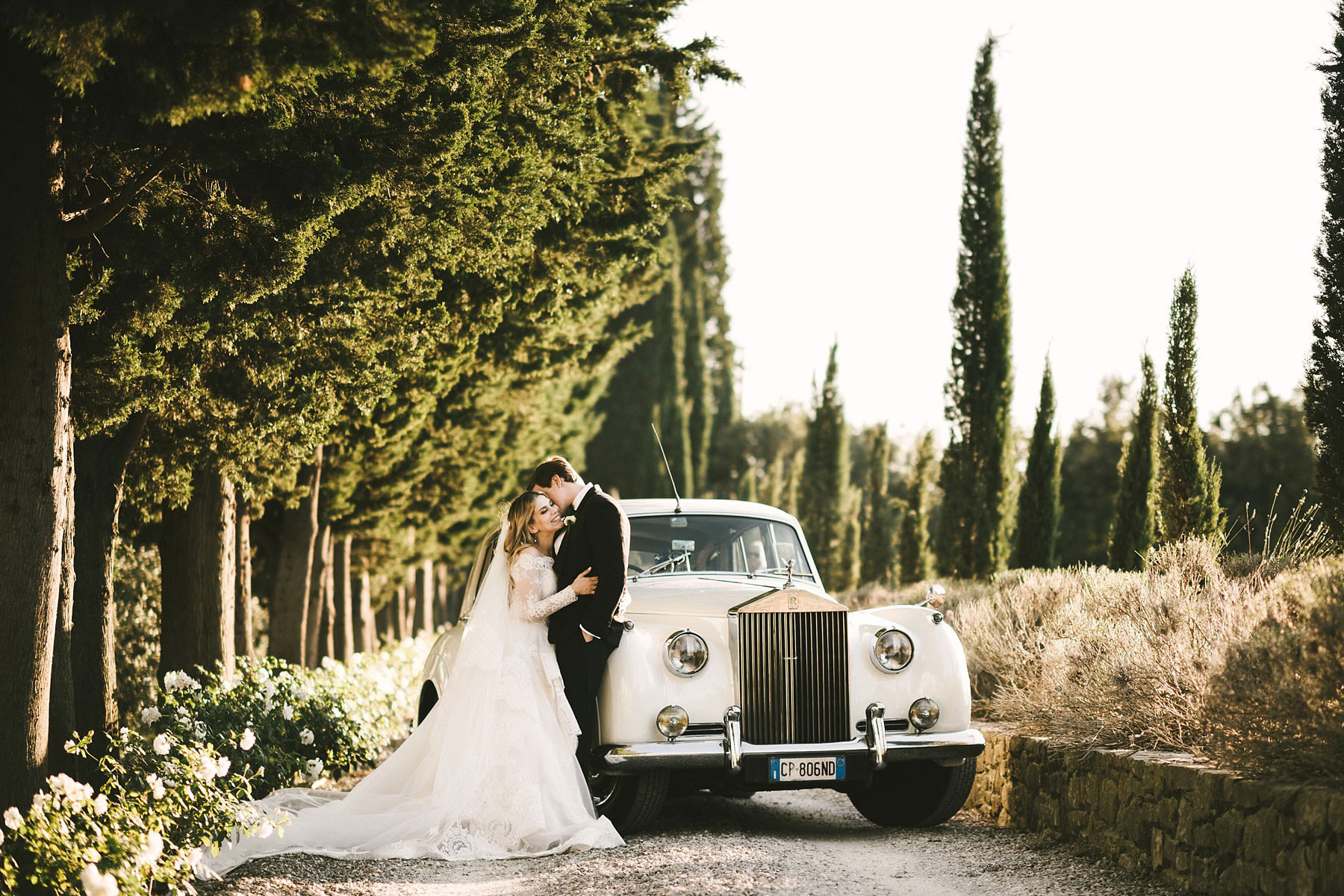 Unforgettable bride and groom photo at Villa Mangiacane with lovely old vintage Roll Royce car. Bridal dress by Justin Alexander