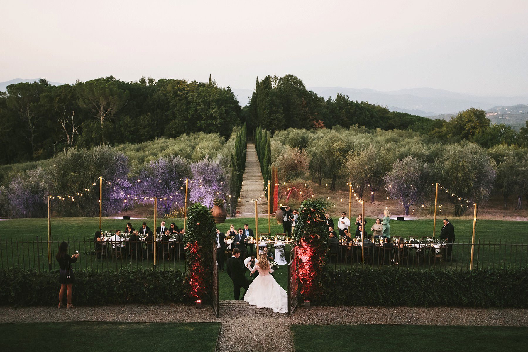 Bride and groom walks to the reception dinner table at Villa Mangiacane. What a lovely view of Olive trees in the Chianti shire in Tuscany