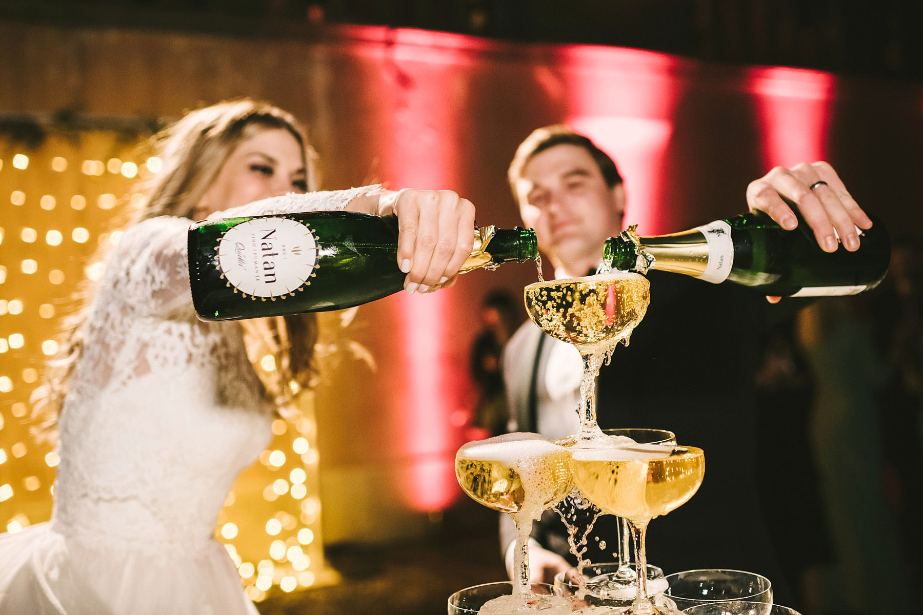 Bride and groom enjoy some time with the pyramid of champagne just before the cut of the cake