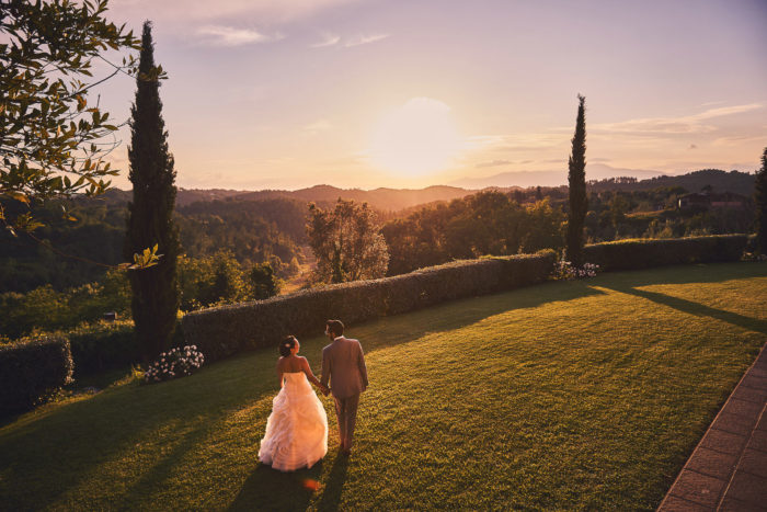Lovely bride groom portrait walking under Tuscan warm golden sun toward the spectacular countryside