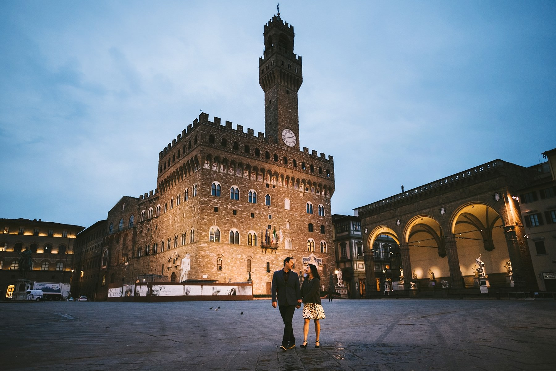Sweet engagement session in Florence with a unique touch. Remember a special vacation and to have pre wedding photos unlike any other. Couple portrait at blue hour in Piazza della Signoria just before the appearance of the sun