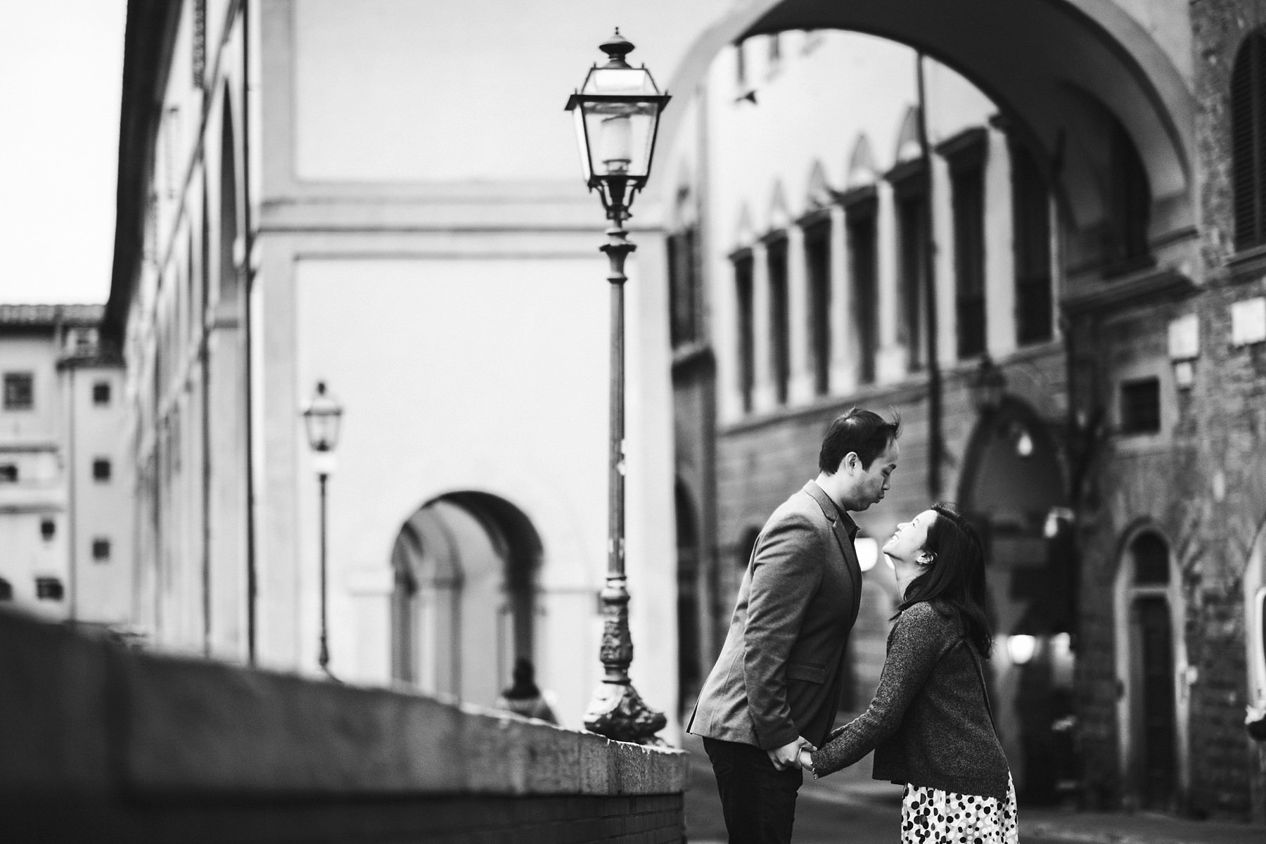 Fun and exciting pre-wedding engagement photo shoot in Florence during the delicate sunrise light time near Ponte Vecchio and Uffizi Art Gallery