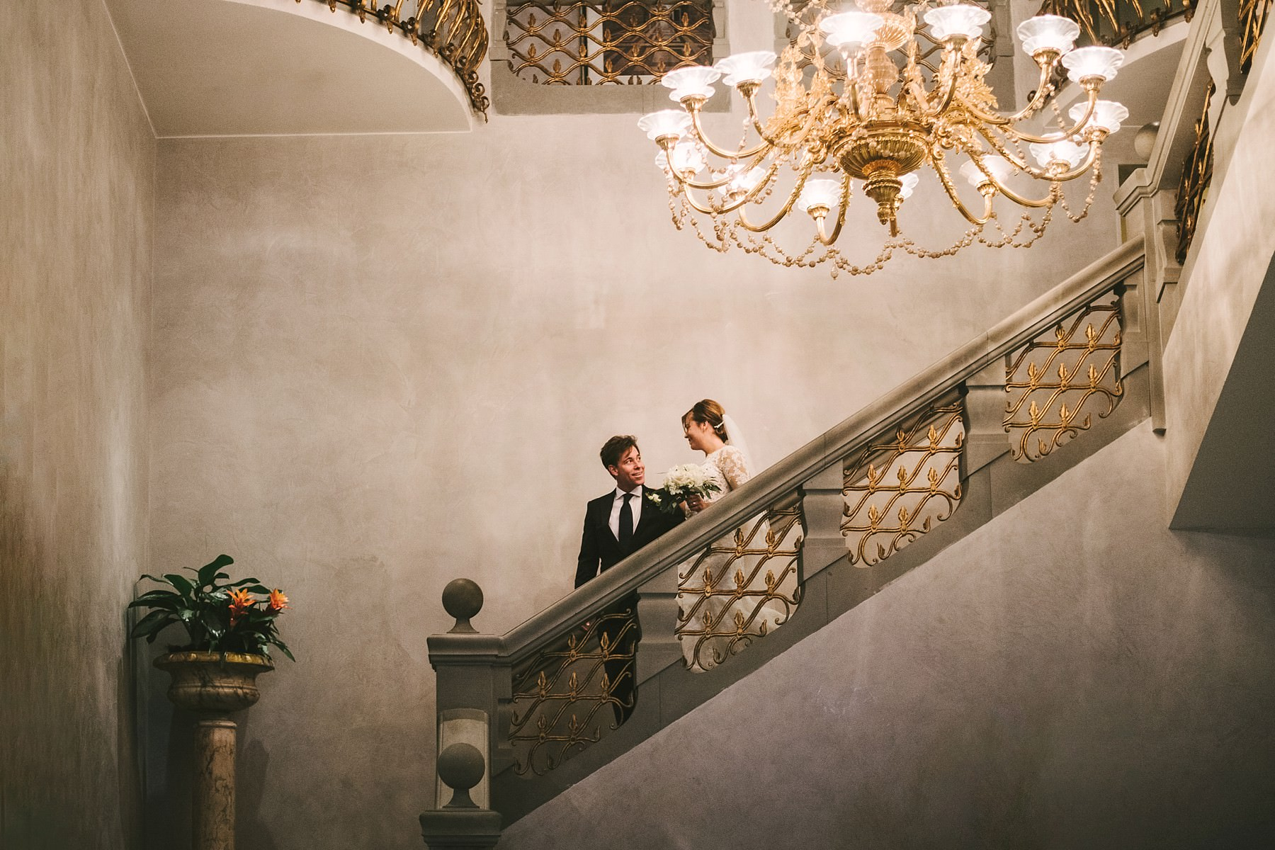 Candid wedding photo with bride and groom walk down the staircase from Sala delle Feste Ballroom at Luxury hotel St. Regis Florence