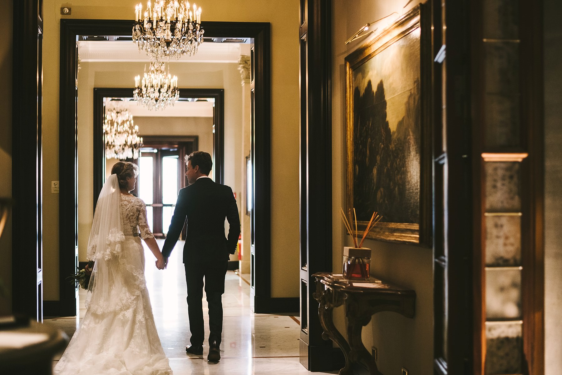 Bride and groom walk away into the luxury hotel St. Regis Florence hall