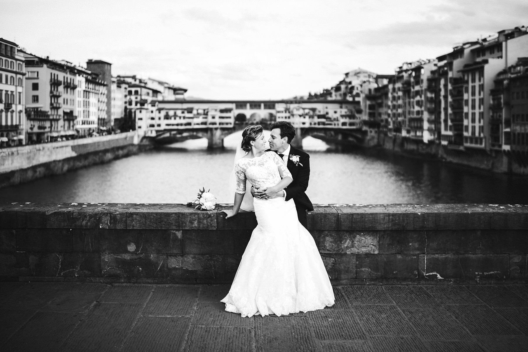 Lovely bride and groom wedding photo at Ponte Vecchio near Uffizi museum. Intimate and elegant destination wedding at luxury hotel St. Regis Florence