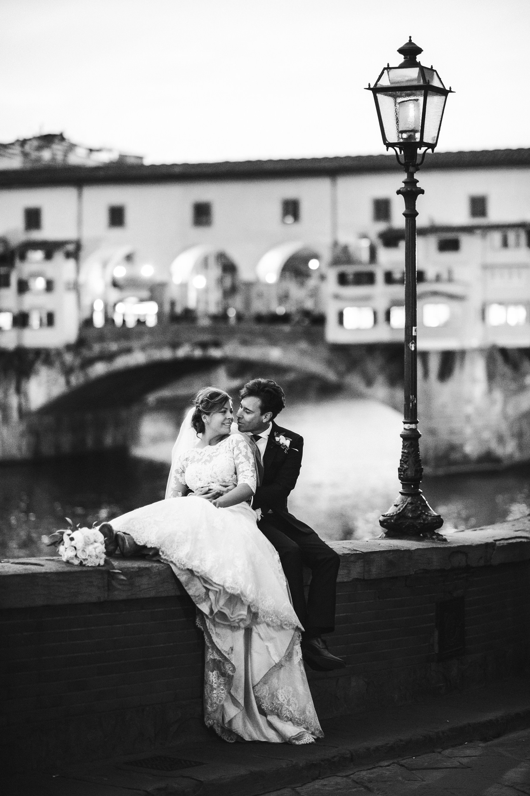 Elegant and romantic wedding photo by bride and groom near Ponte Vecchio. Luxury and elegant intimate destination wedding in Florence at Hotel St. Regis