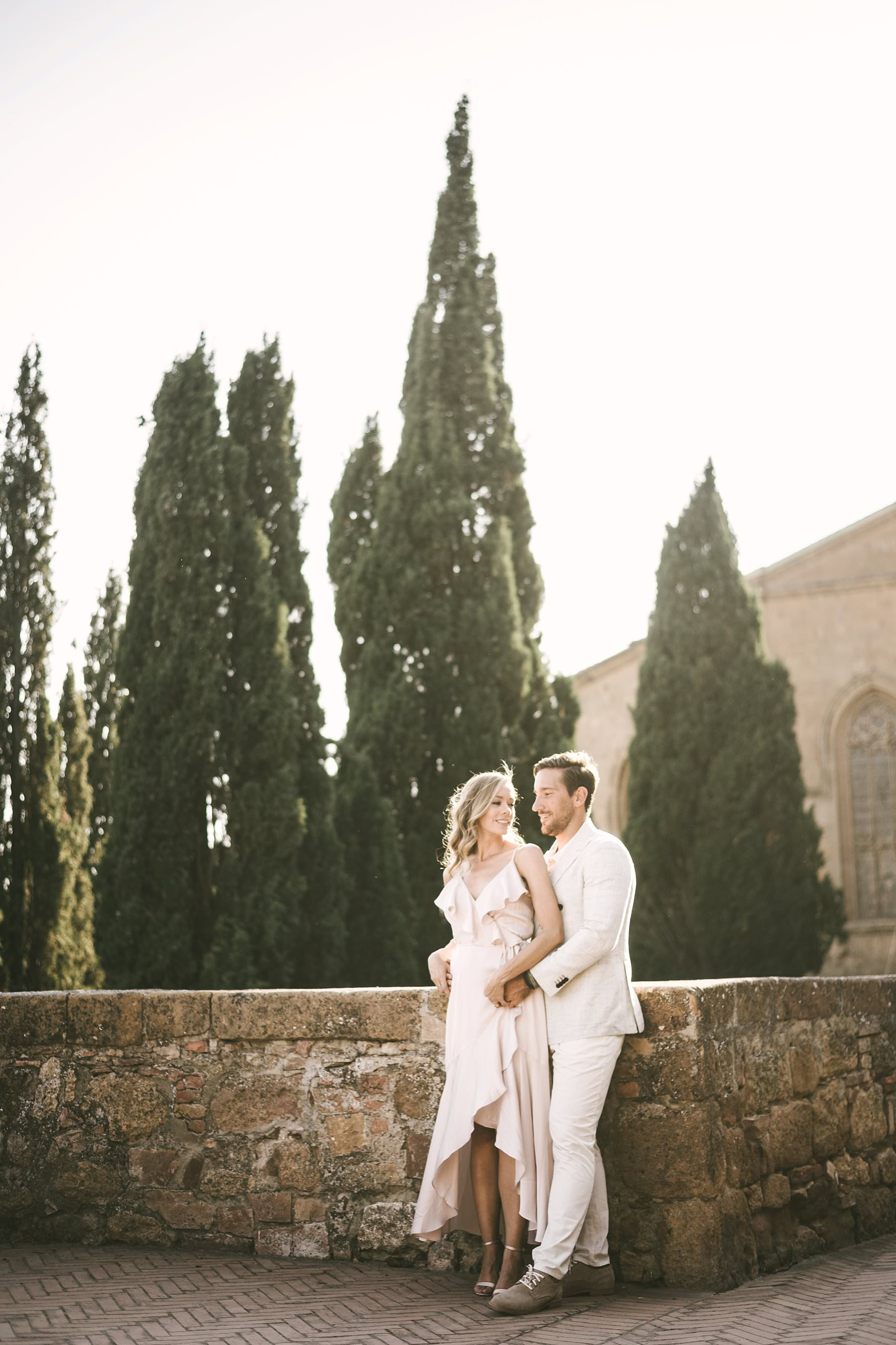 Lovely tuscan typical couple photo with cypress in the background in the town of Pienza