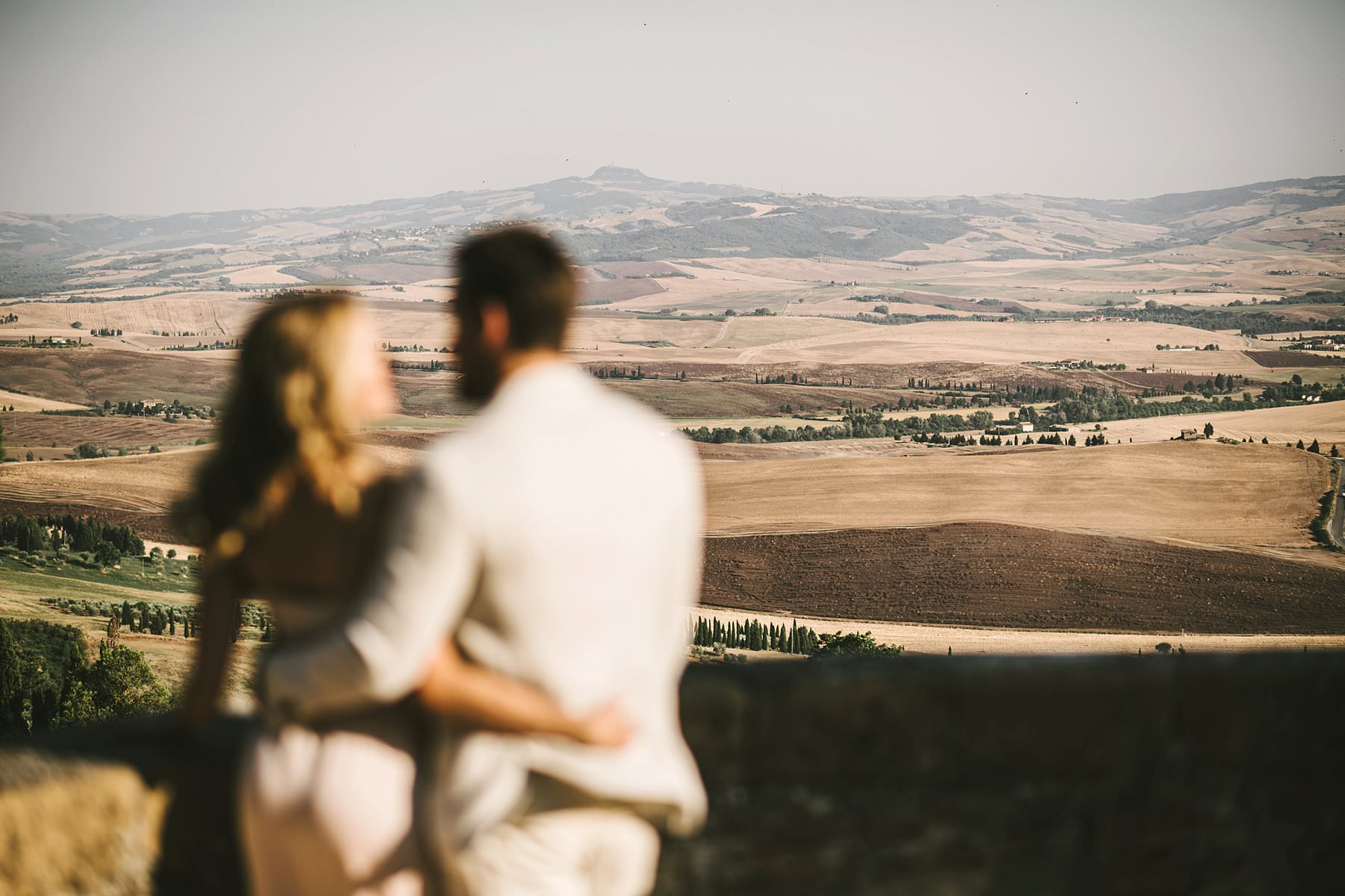 Romantic and intimate couple eloping in Tuscany countryside of Val D'Orcia with rolling hills as background