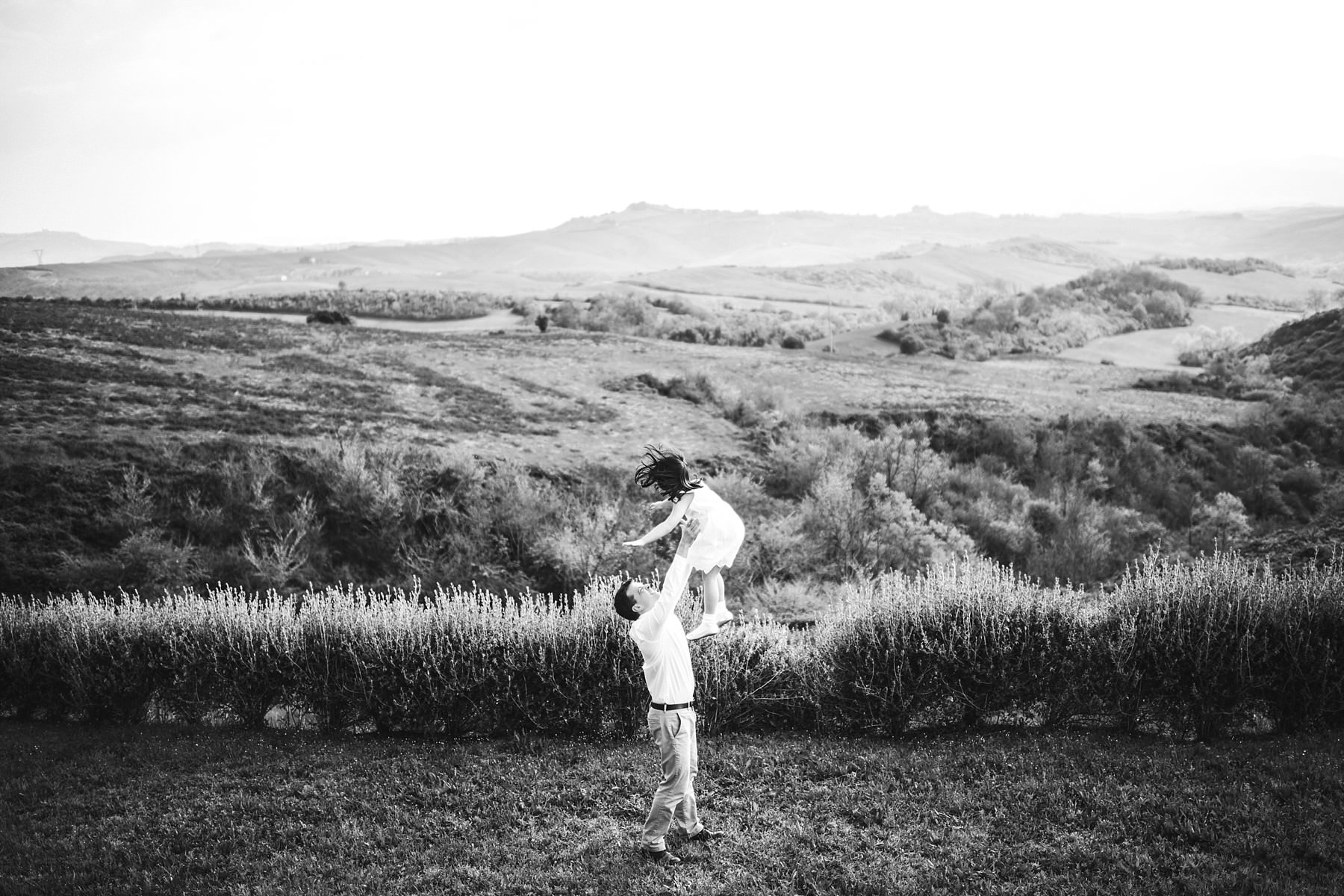 Dad and daughter are playing during a family photo session took place in a summer day in Tuscany countryside