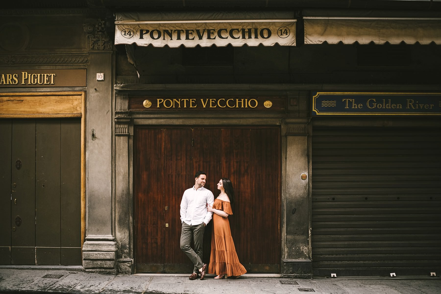 Gorgeous romantic and elegant couple portrait at Ponte Vecchio, Florence at sunrise time. Romantic experience with anyone around the couple