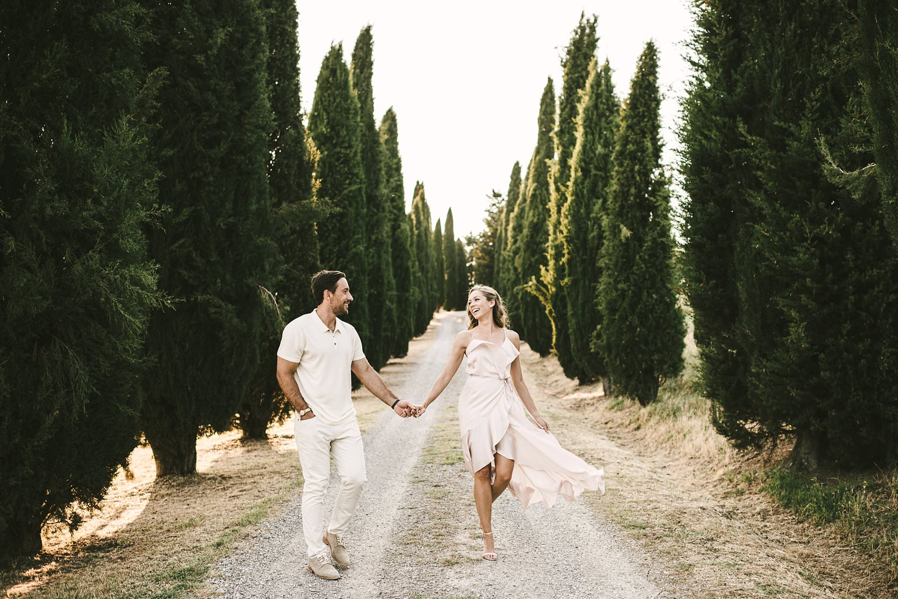 Elegant and romantic engagement experience in the Val D'Orcia area of Tuscany near Pienza with cypresses street in the countryside