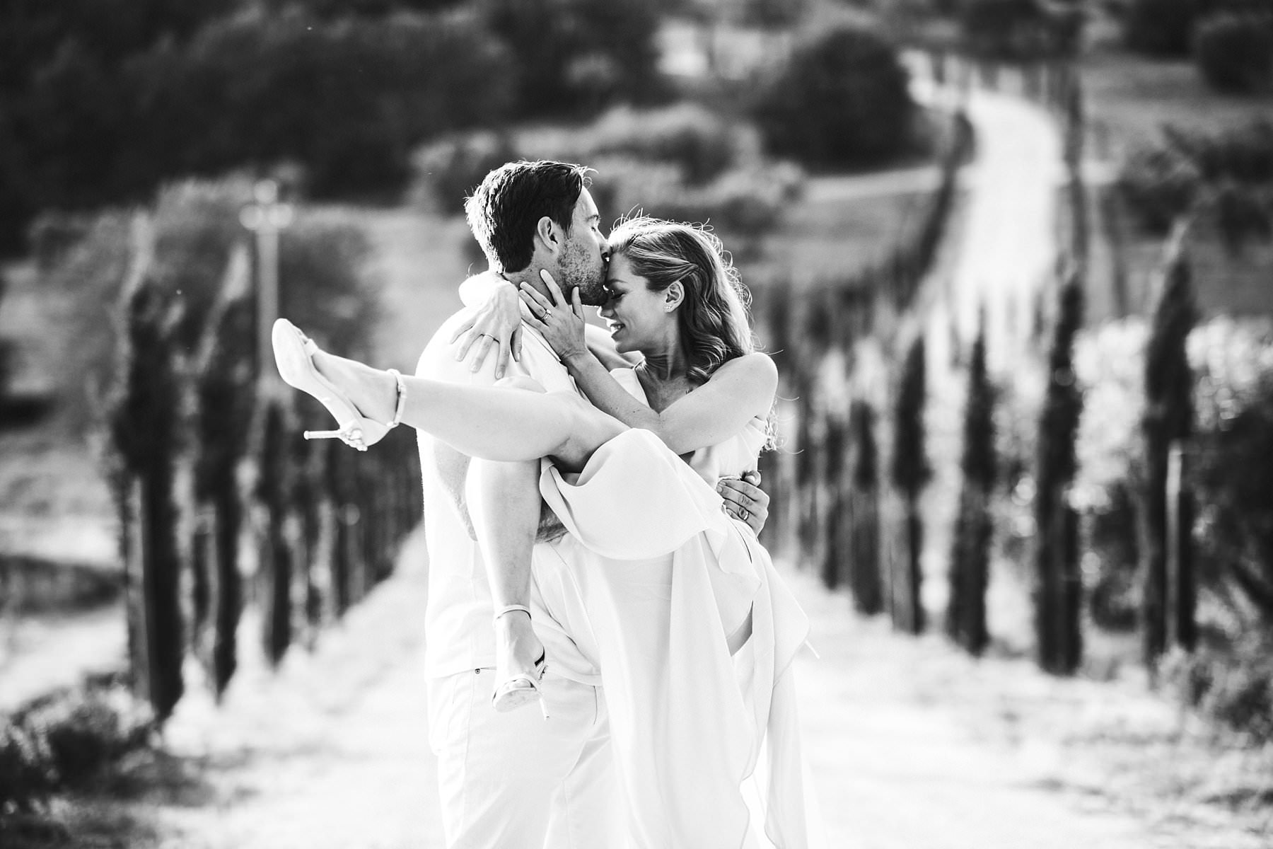 Dreamy Italy elopement with vows renewal in Val d'Orcia. Unforgettable couple portrait photo with cypresses street and rolling hills typical of the Tuscany countryside of Pienza