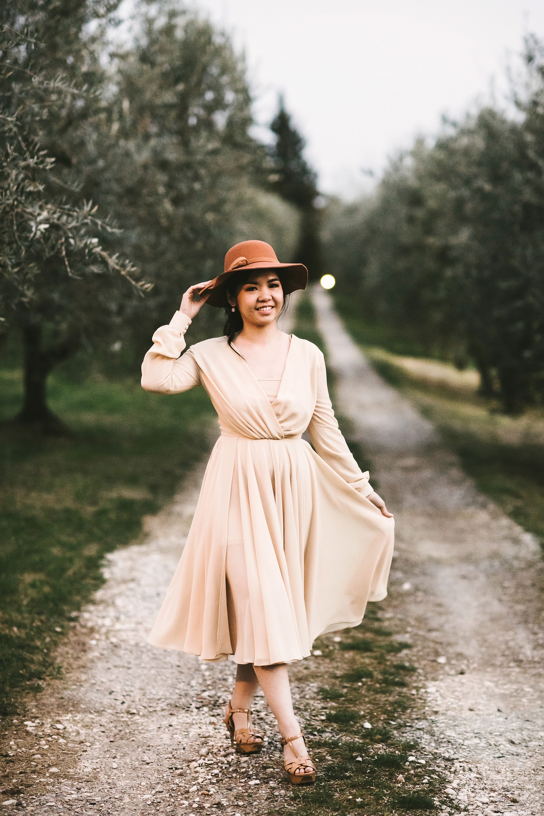 Lovely Natania pose for engagement couple photo shoot in Chianti area of Tuscany countryside into a white street near Olive trees field