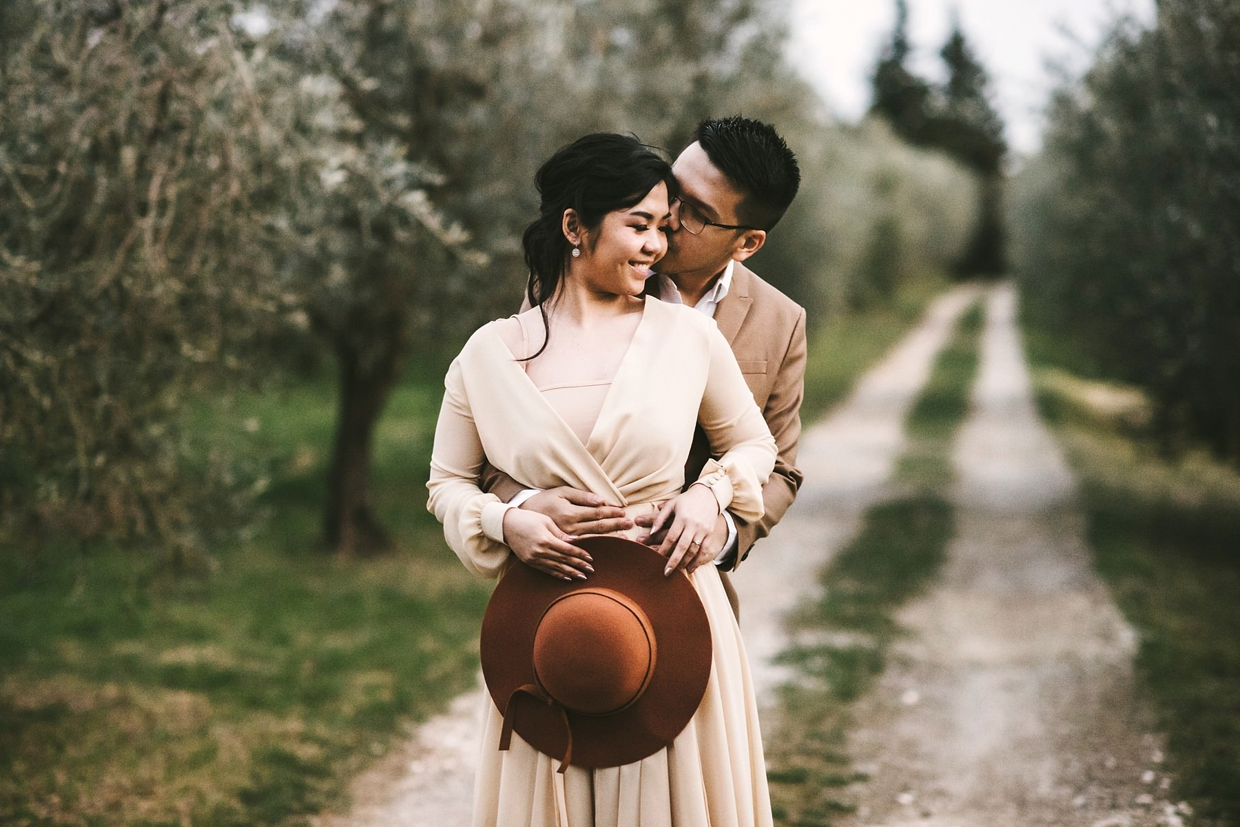 Beautiful and intimate couple in their engagement pre wedding photo session in charming olive trees field in the Tuscany countryside in Chianti