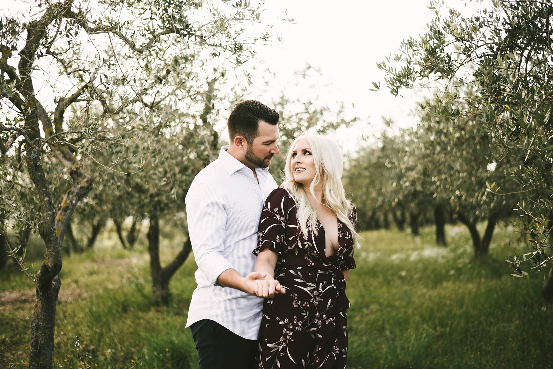 Emotional couple portrait honeymoon photo shoot in Tuscany olive trees field at unforgettable venue of Castella La Leccia