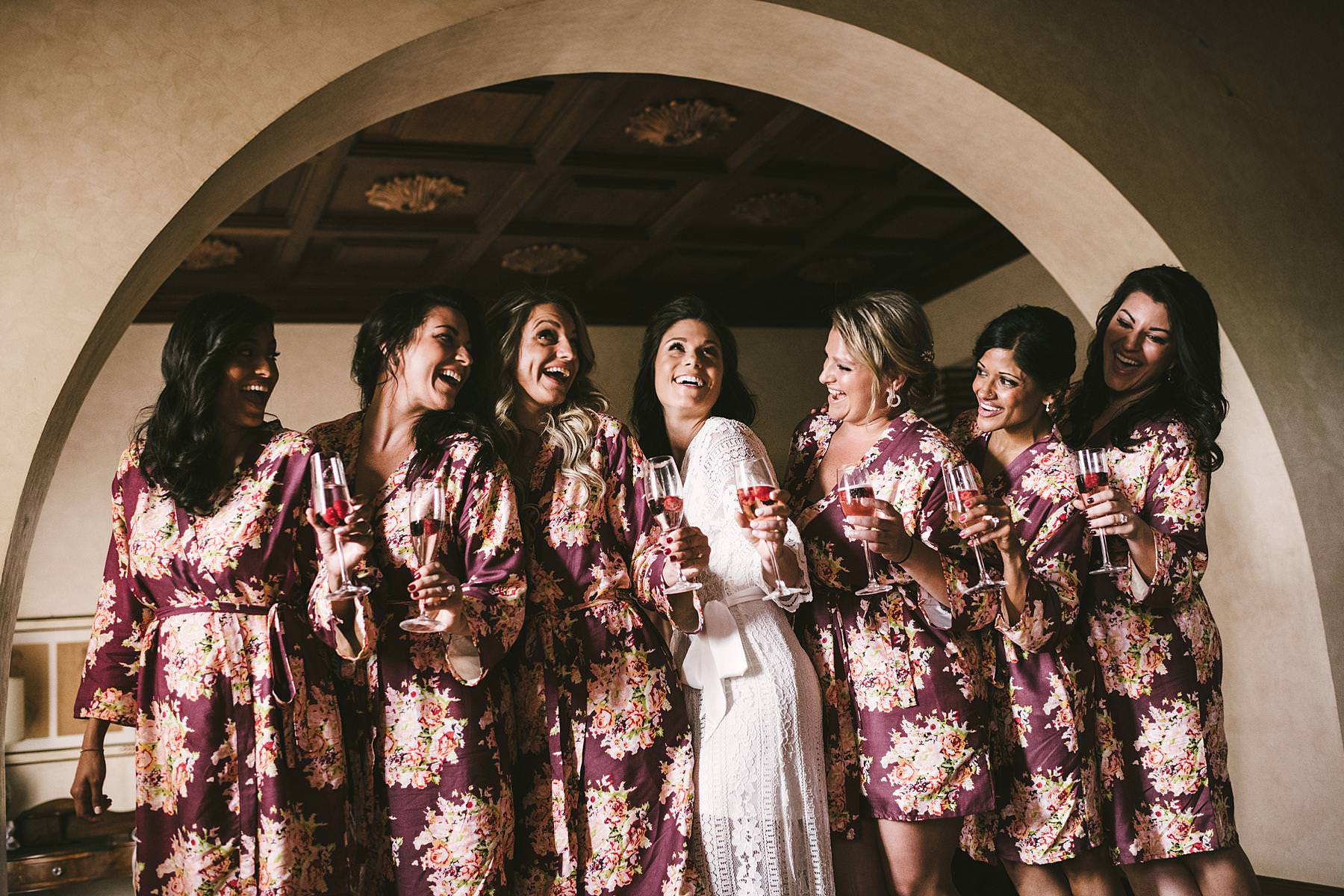Bride and bridesmaids exciting portrait before to walk down the aisle. Elegant destination wedding in Tuscany countryside at the historic estate of Villa La Selva Wine Resort