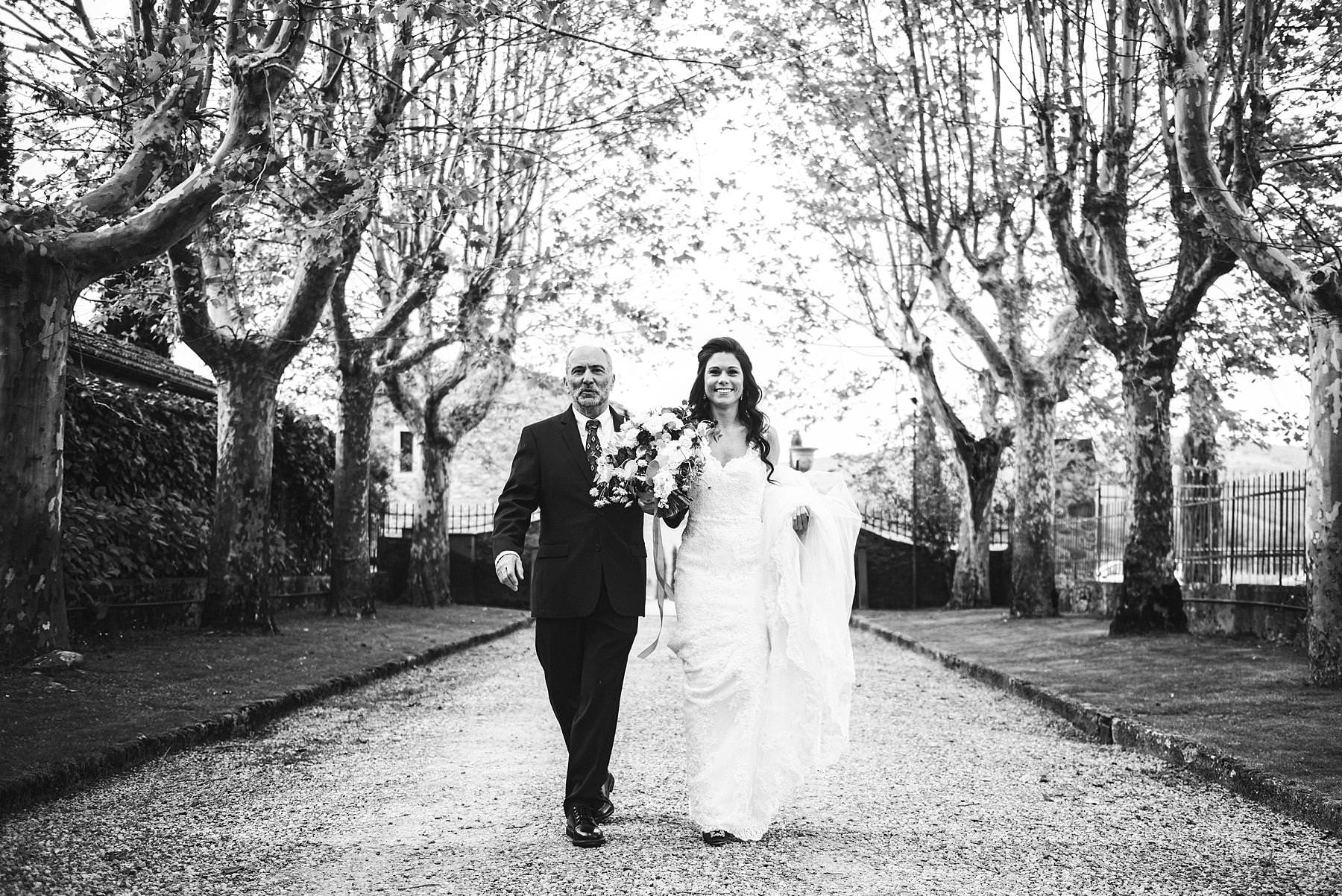 Lovely bride walks with father toward the outdoor ceremony aisle at Villa La Selva Wine Resort