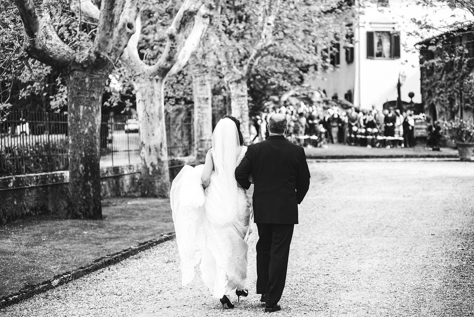 Emotional bride walks to the outdoor ceremony at Villa La Selva Wine Resort historic estate
