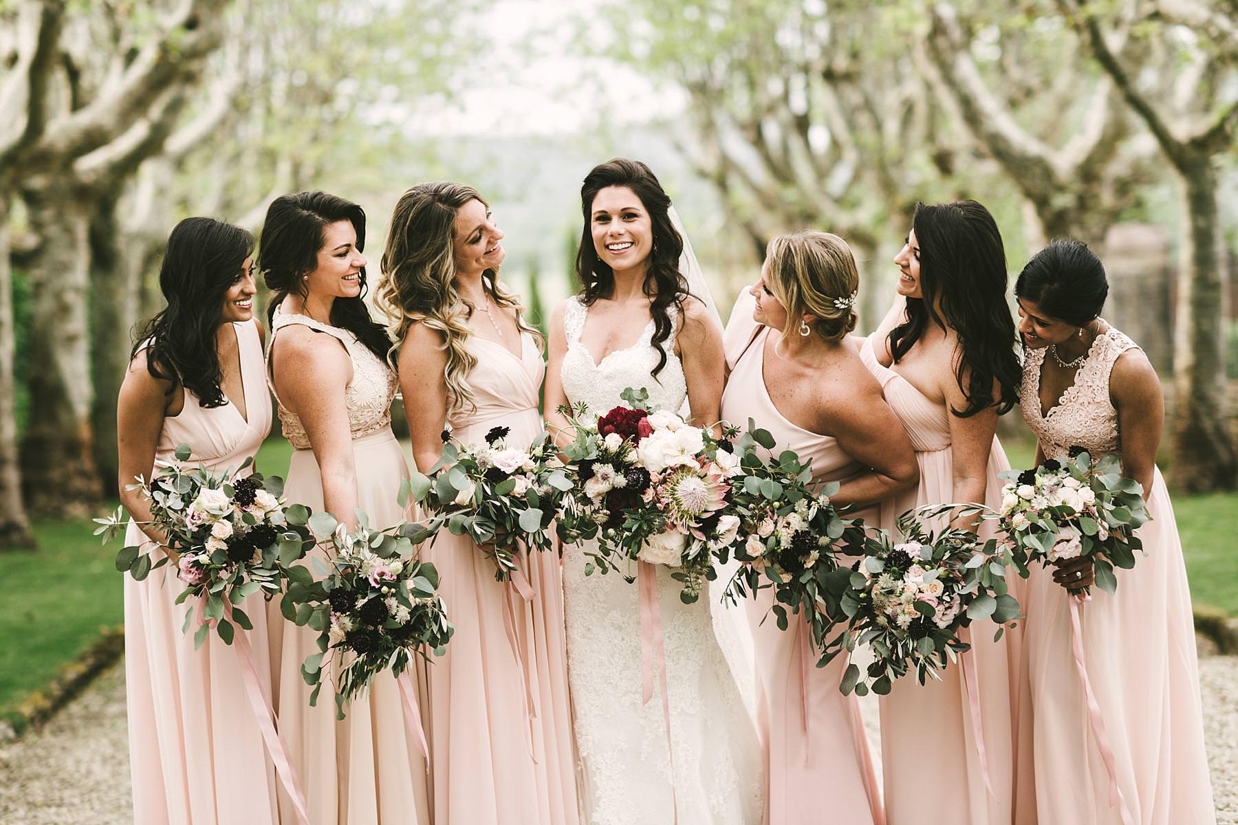 Bride in Pronovias wedding gown and bridesmaids photo. Elegant white, green, rose colours destination wedding in Tuscany at historic venue of Villa La Selva Wine Resort