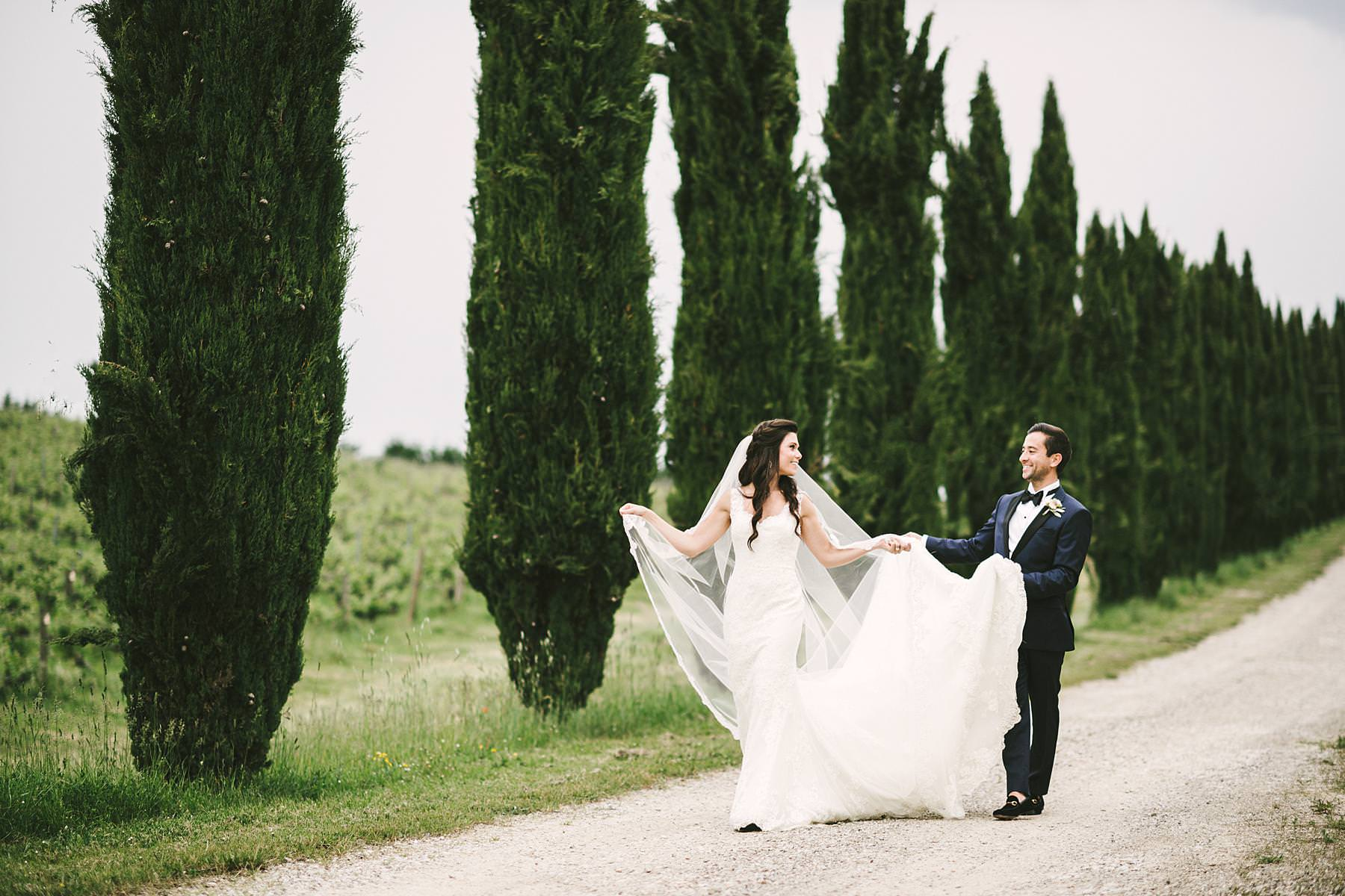 Beautiful and elegant bride and groom wedding portrait at Villa La Selva Wine Resort historic estate evocative cypresses street in Tuscany countryside