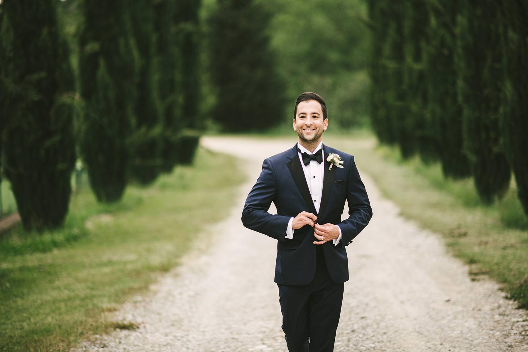 Elegant groom wedding portrait Tuscany countryside destination wedding event