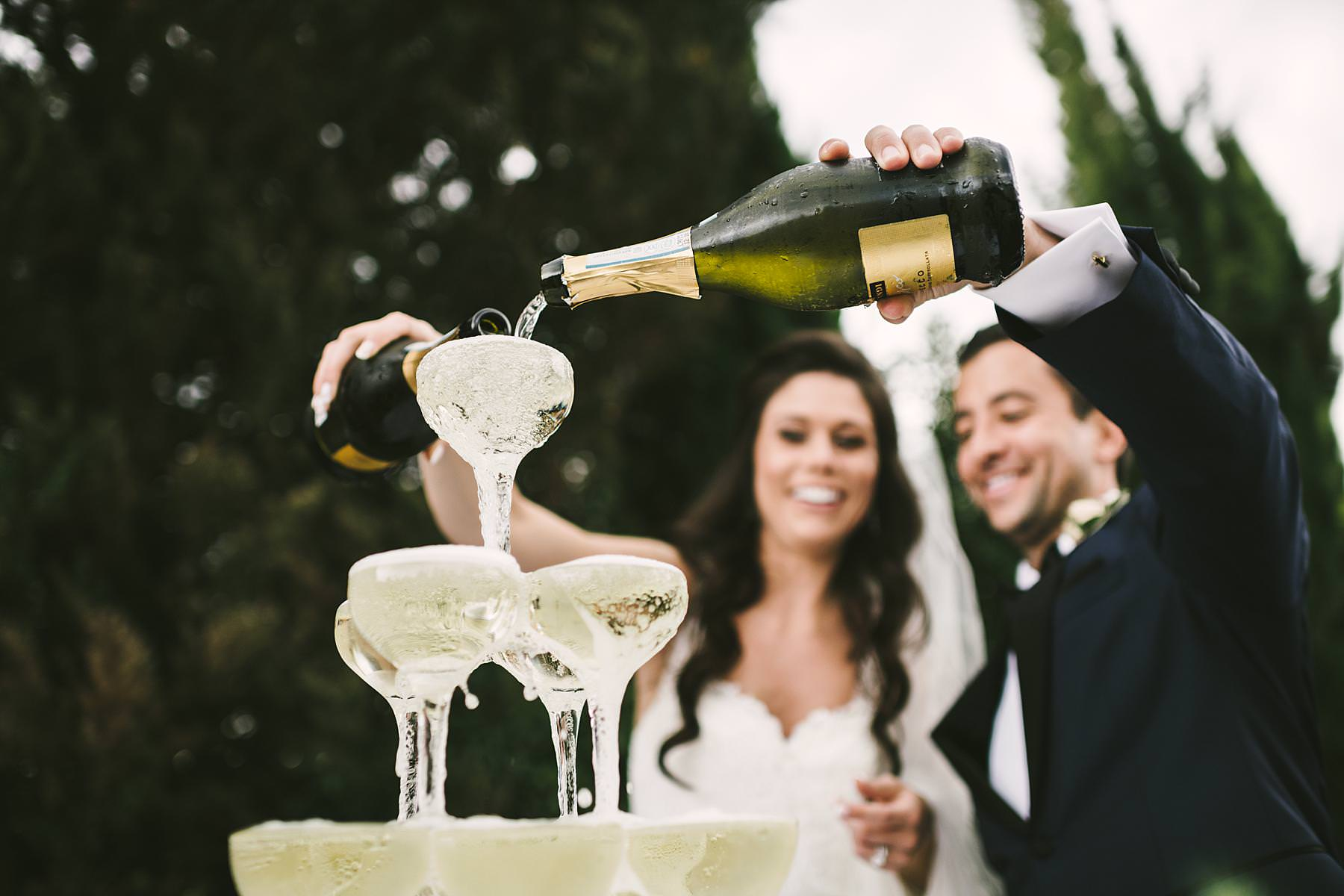 Exciting champagne pyramid toast during destination wedding cocktail event at Villa La Selva Wine Resort in Tuscany countryside