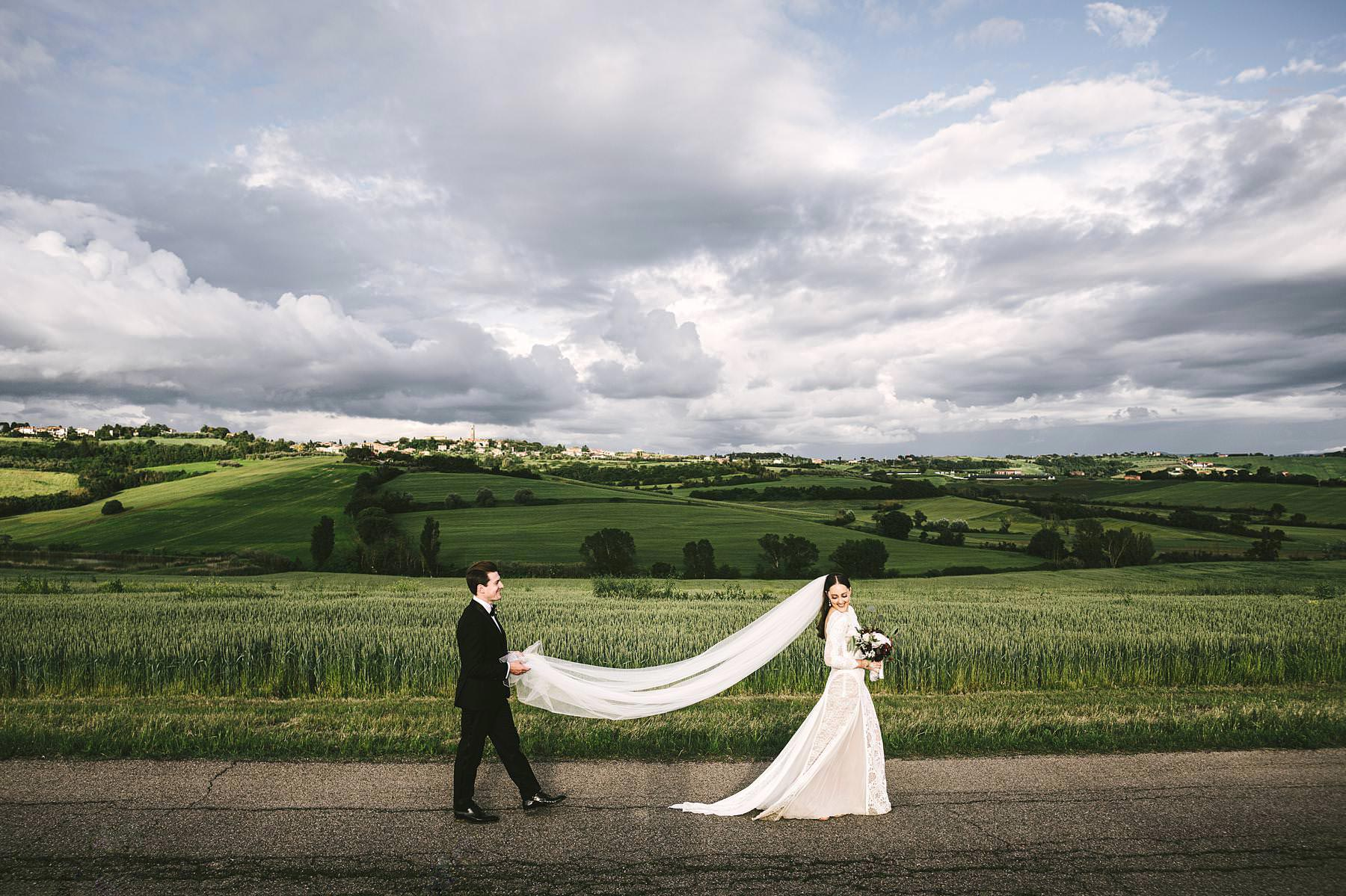 The amazing landscape of Umbria near the historic venue of Villa l'Antica Posta. Exciting bride in Grace Loves Lace with groom in their intimate destination wedding