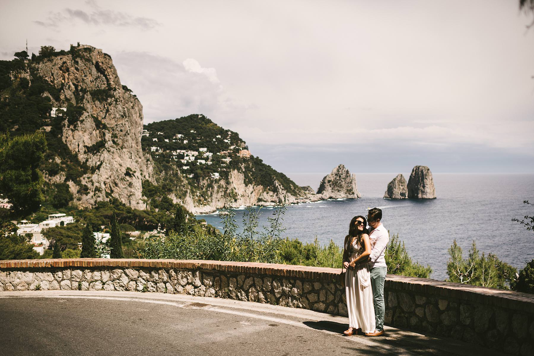 Couple portrait engagement pre-wedding photo session in a scenic road with breathtaking sea stacks of Capri island