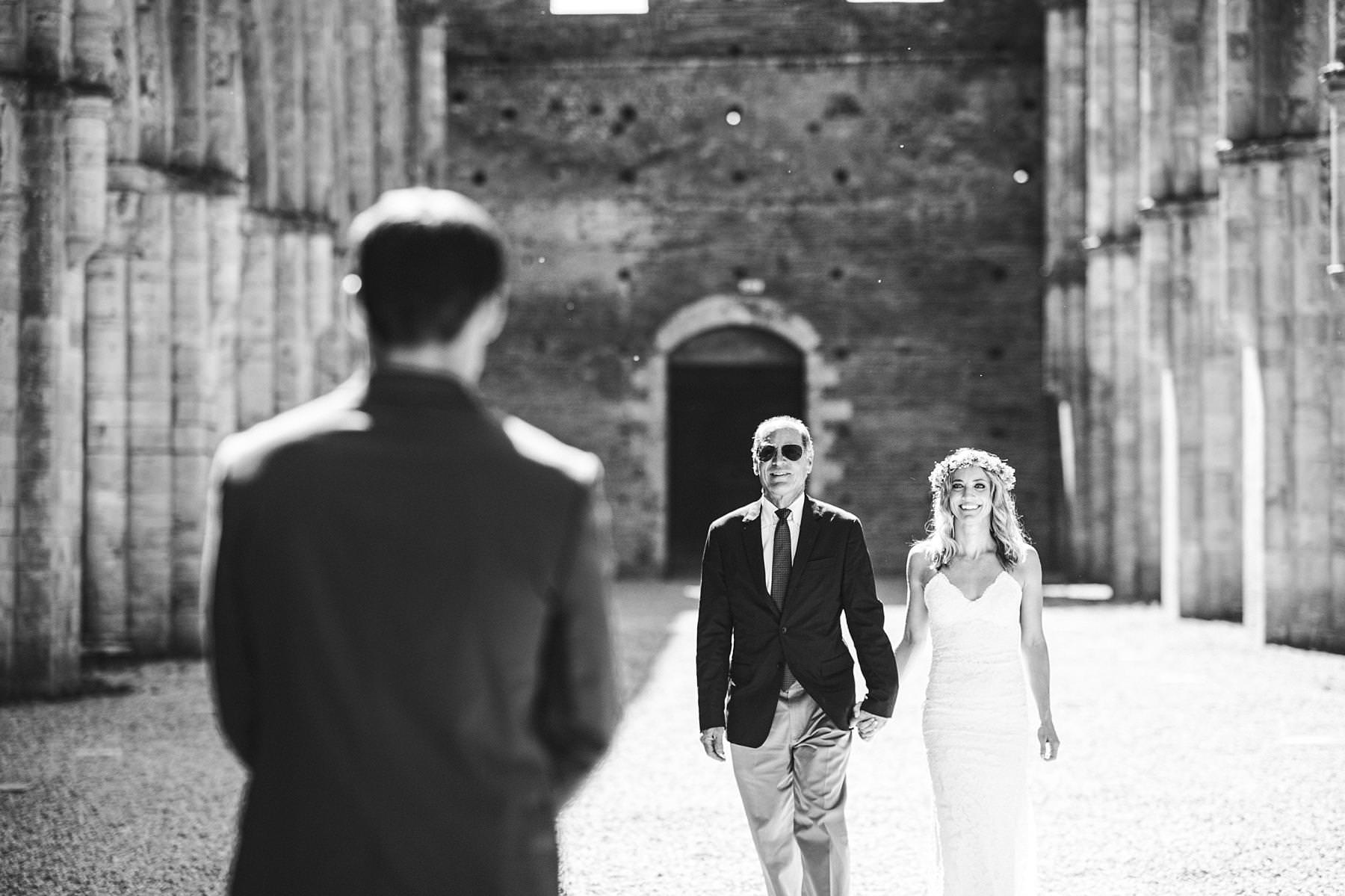 Bride Amelia walks down the aisle of the roofless abbey of San Galgano intimate wedding in Tuscany